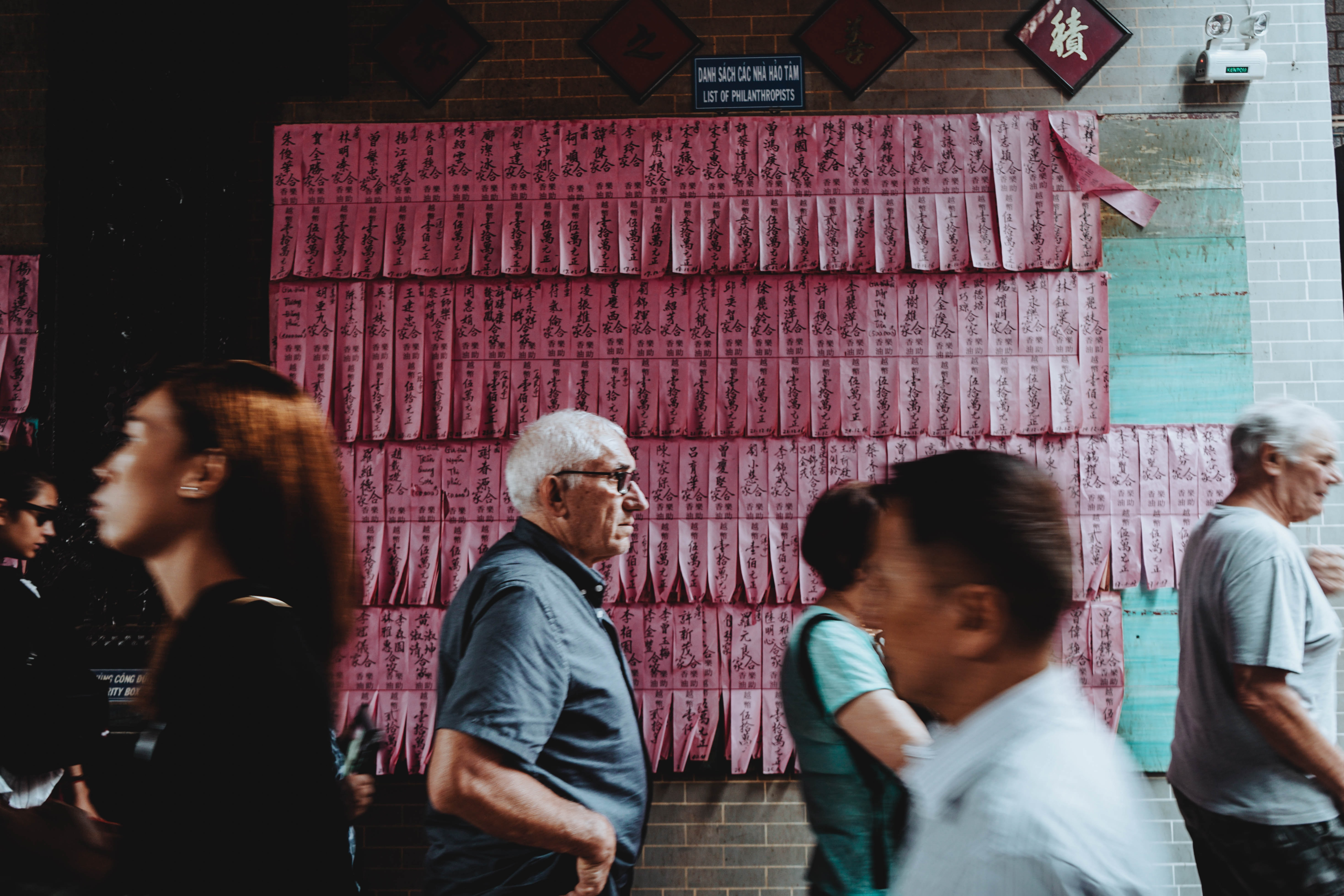 Diverse crowd of tourists walking past a wall of pink paper at a temple