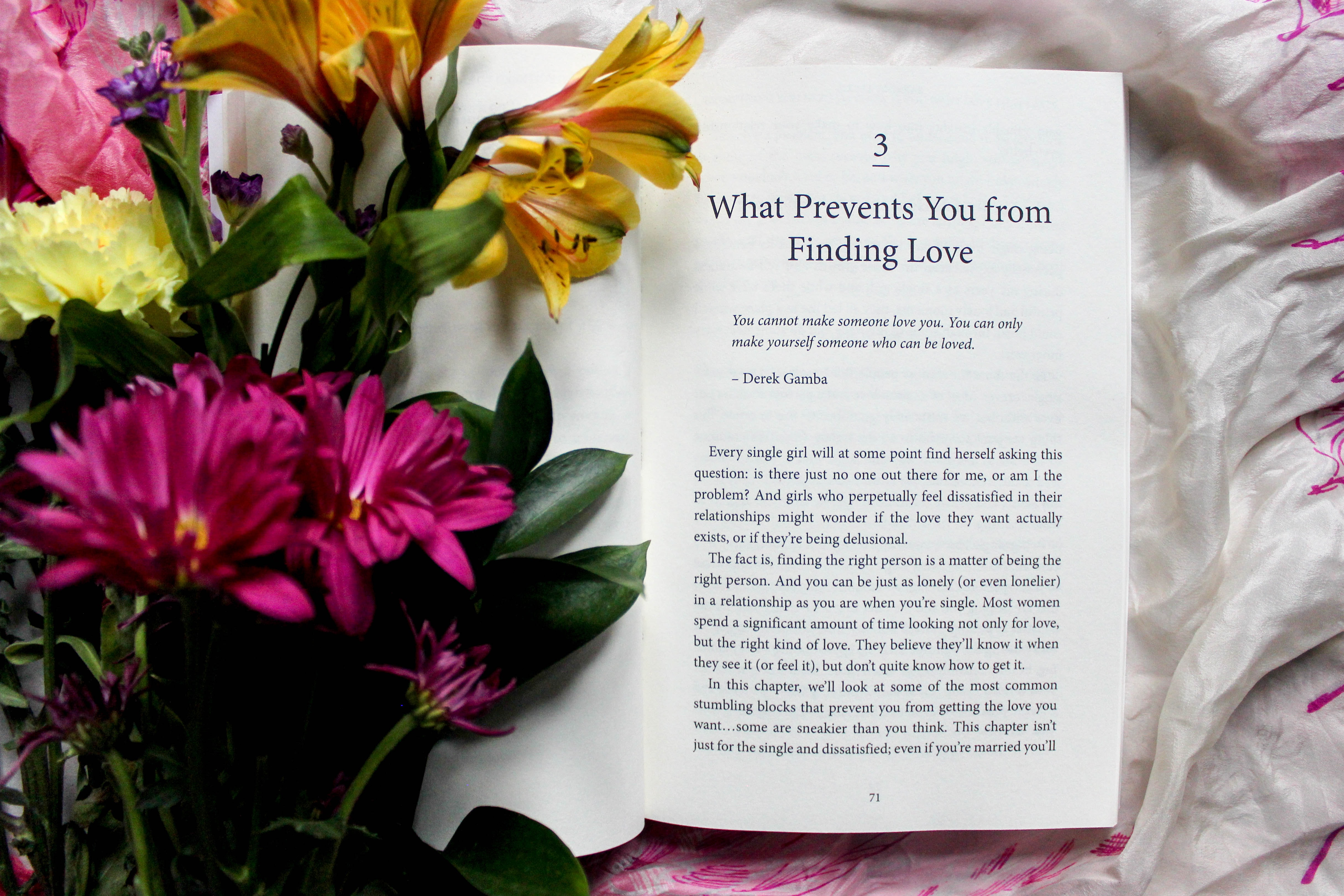 reading book beside pink, yellow, and green petaled flower bouquet