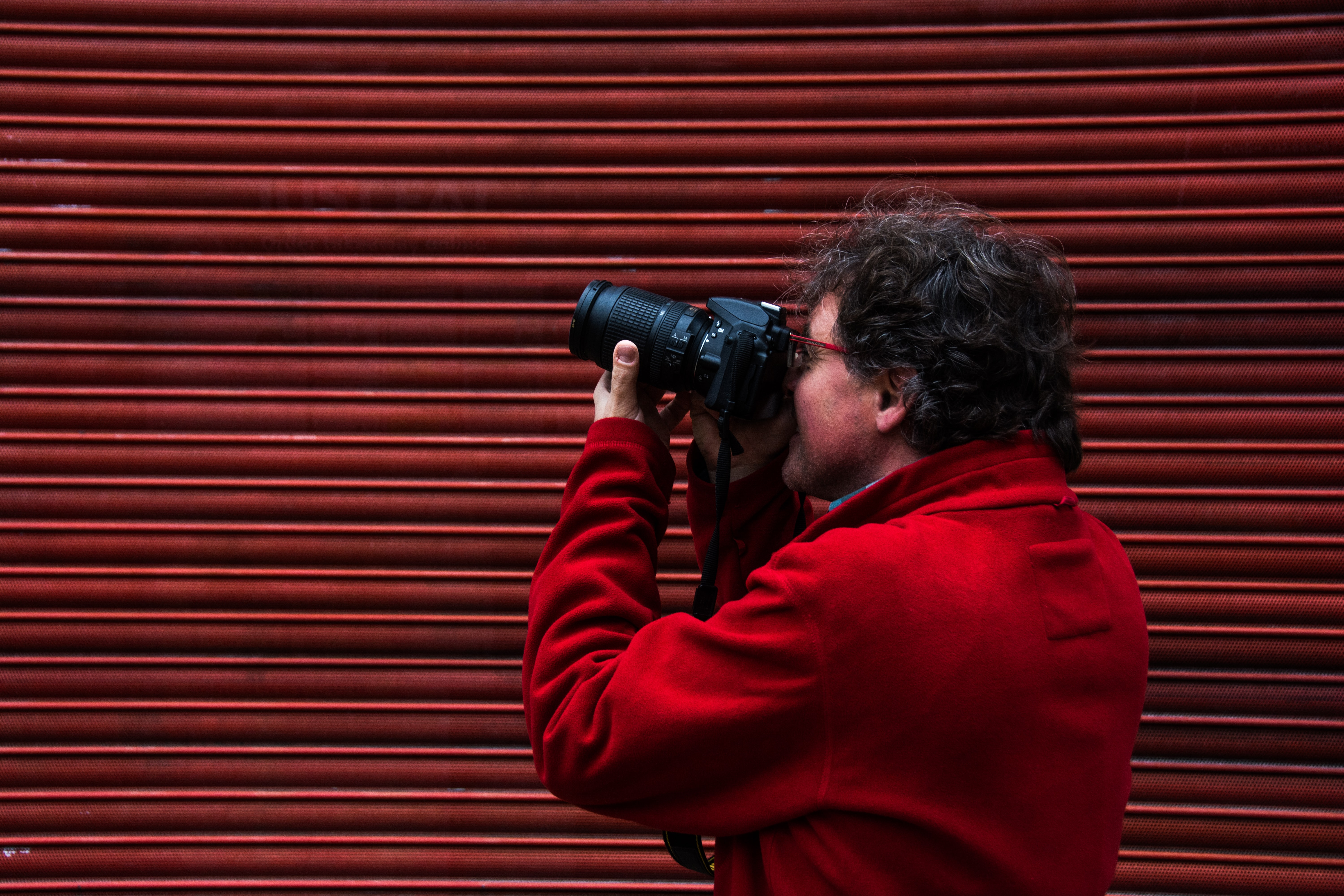 A person in a red jacket points a camera in front of a red wall