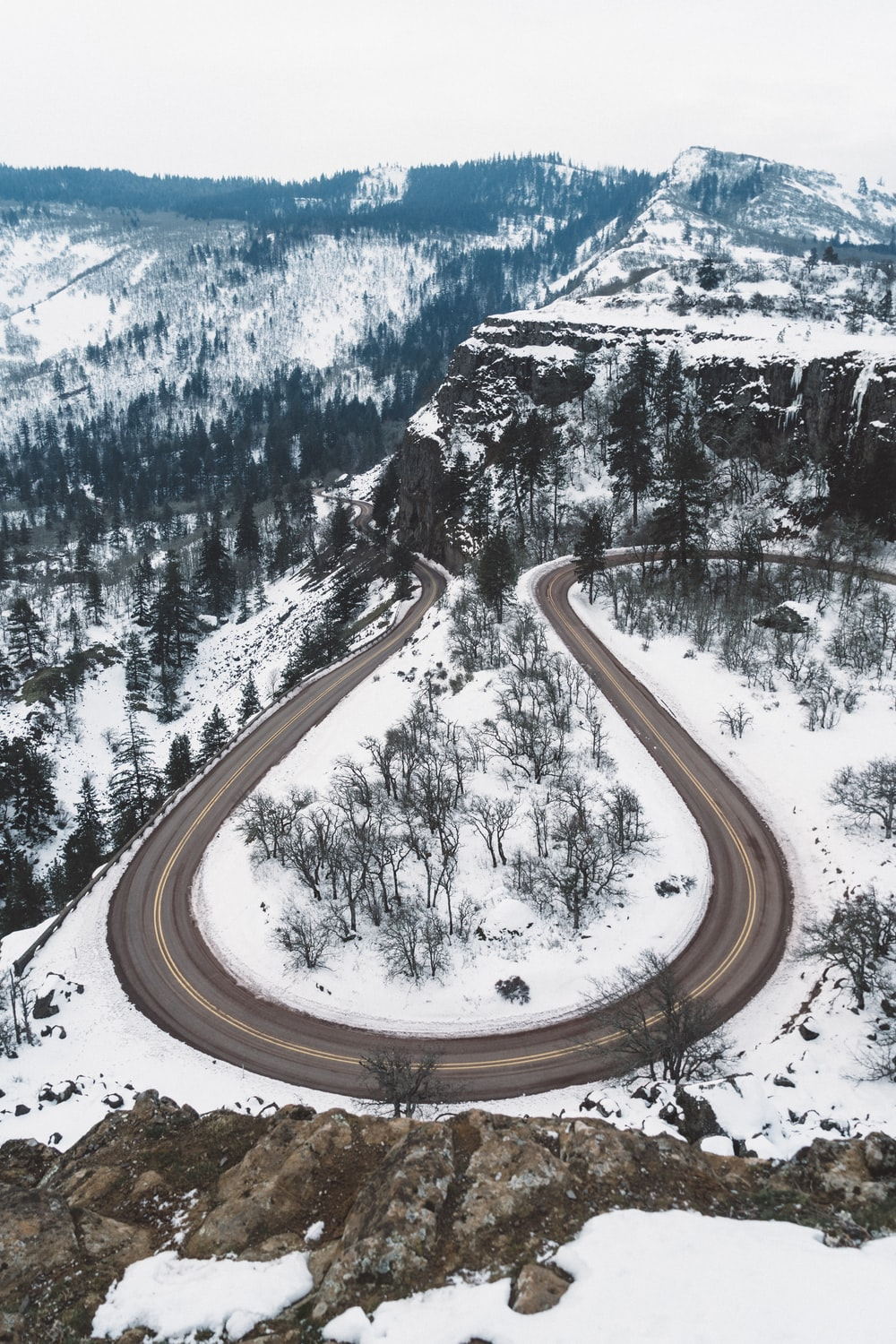 aerial photography of curved road in between snow covered ground overlooking mountain and trees under white sky at daytime