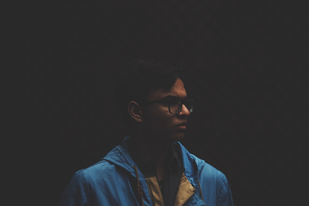 selective focus photo of man with dark background