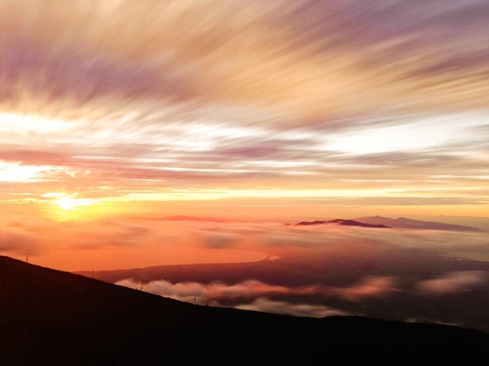 silhouette photo of mountain under orange sky
