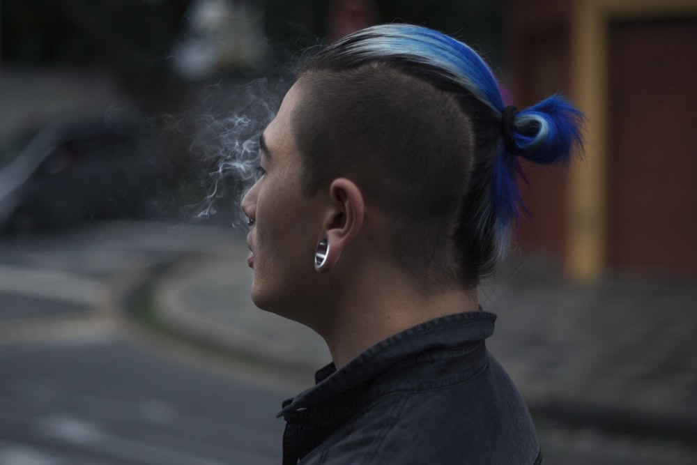 selective focus photography of man with blue mohawk hair