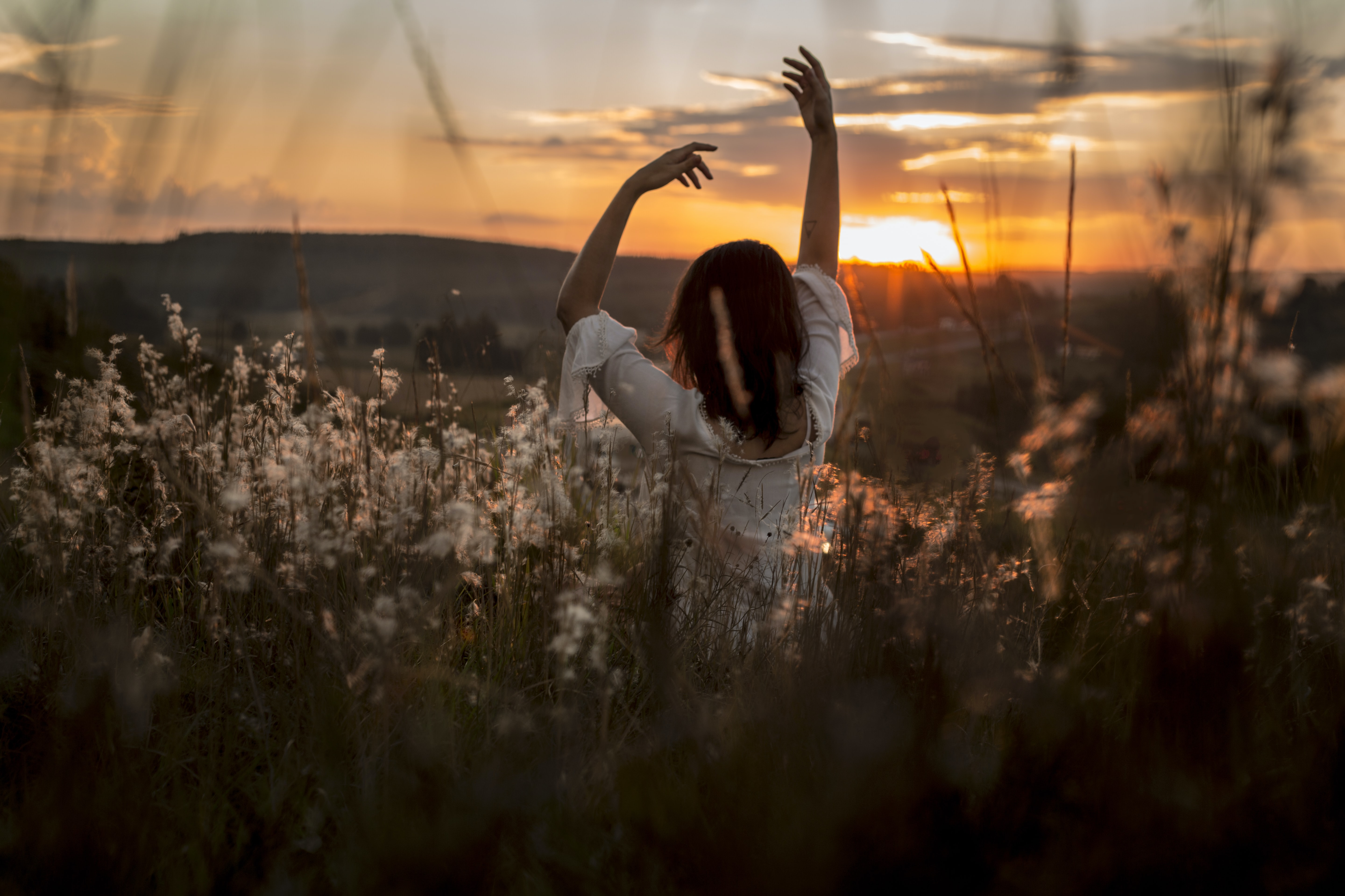 woman wearing white dress raising her two hands surrounded white petaled flowers during sunset