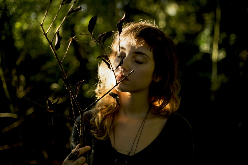 woman wearing black necklace smelling plant during daytime