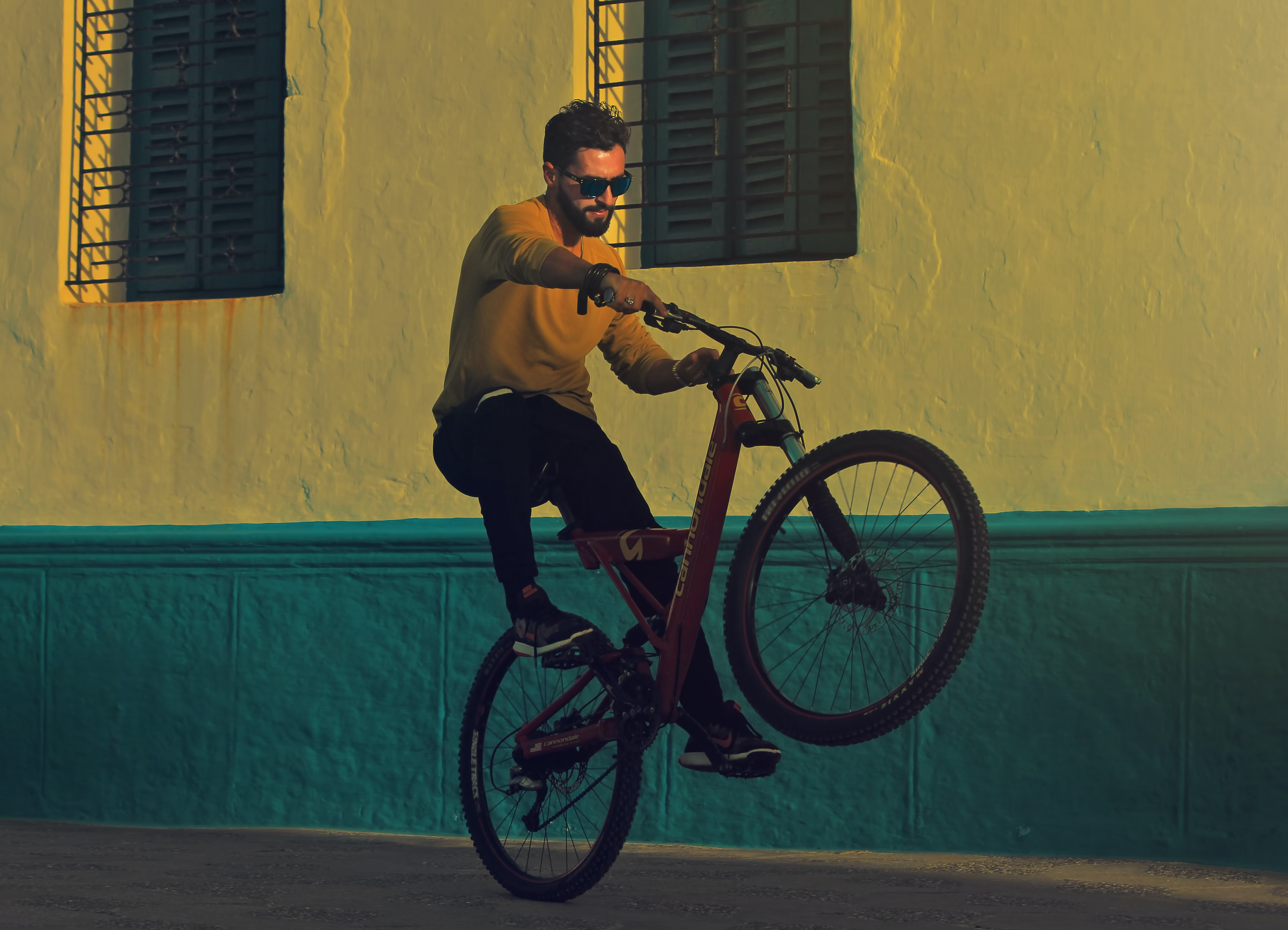 Bearded man in sunglasses doing wheelie on bicycle in front of green and yellow building