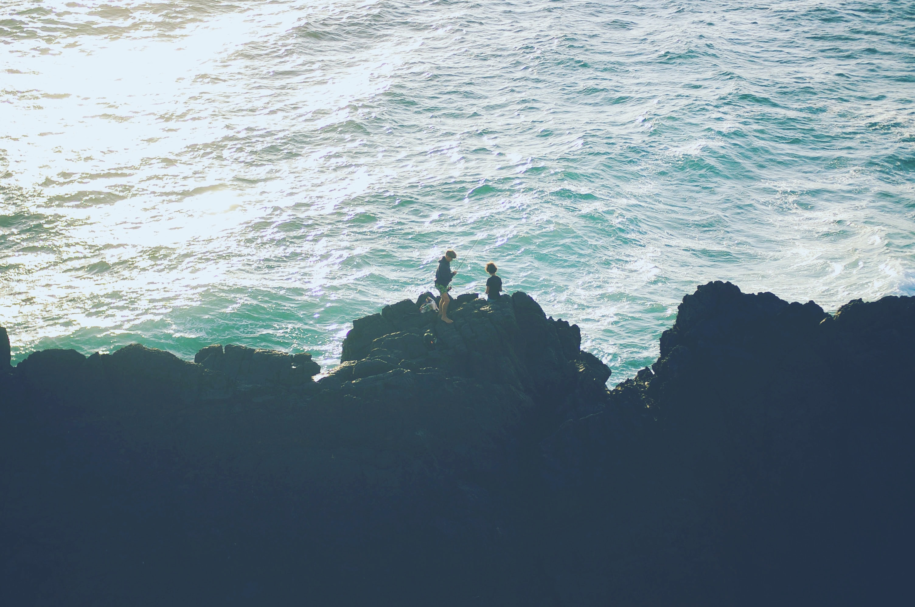 Two people stood on the rocks at the most easterly point of the Australian mainland, with the sea beneath them