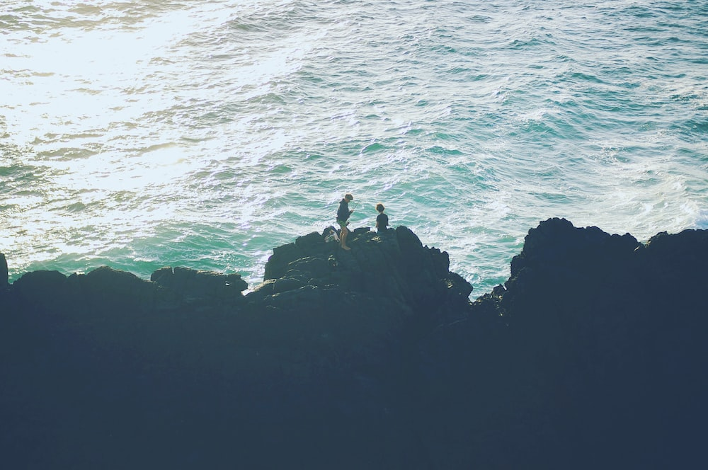 two person standing on the cliff near the ocean