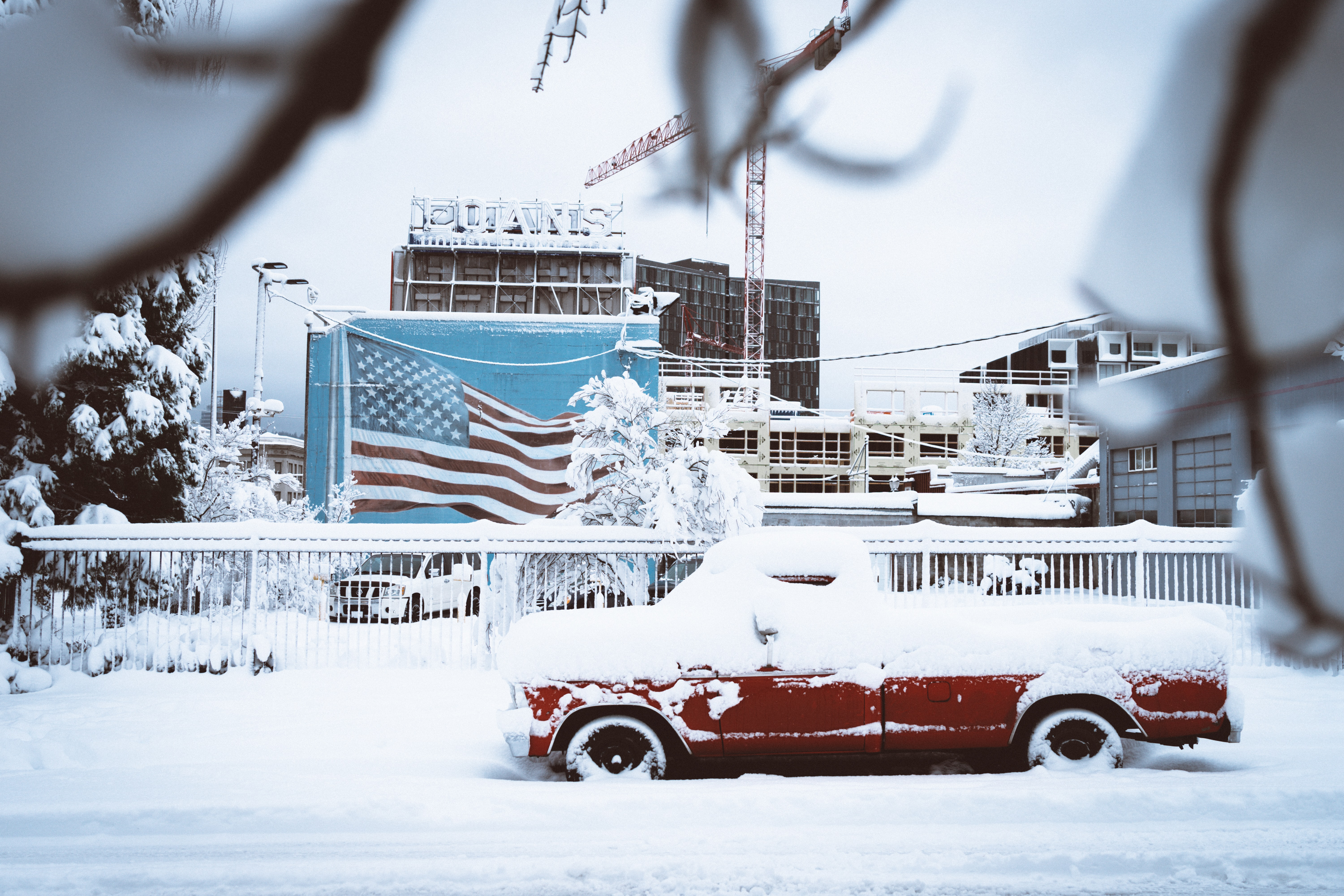 Red truck covered in snow at a harbor in Portland