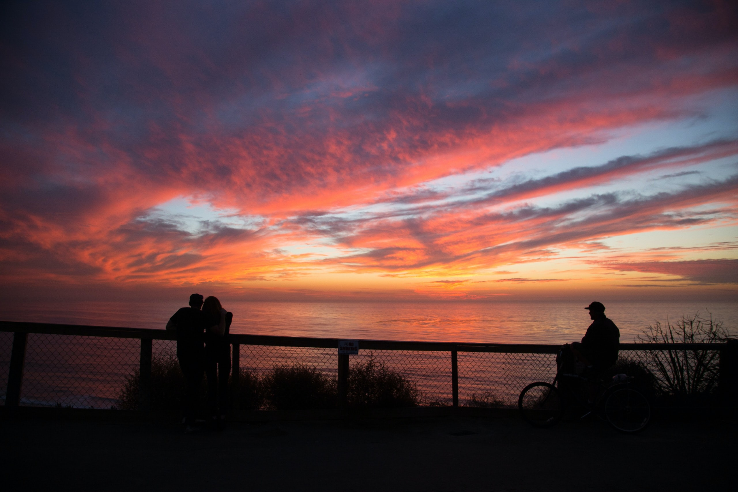 Silhouettes of a couple and a nearby biker watching a warm sunset atop Leucadia Boulevard