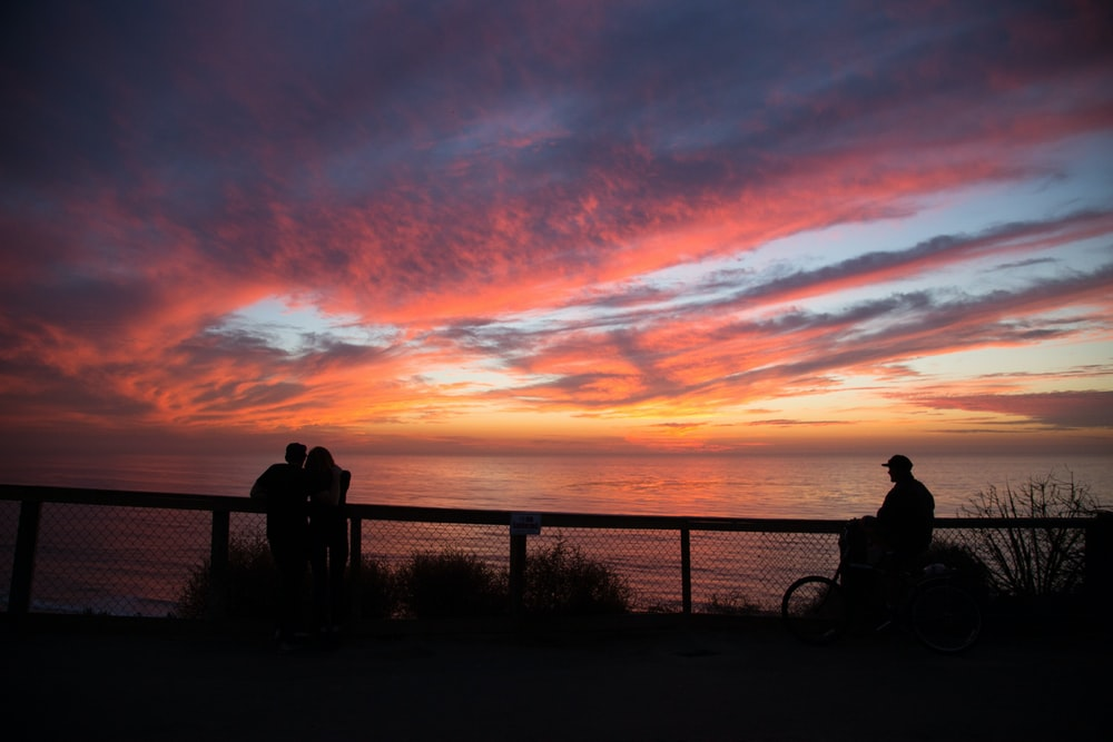 silhouette of people near cliff railings at distance to wide body of water during golden hour