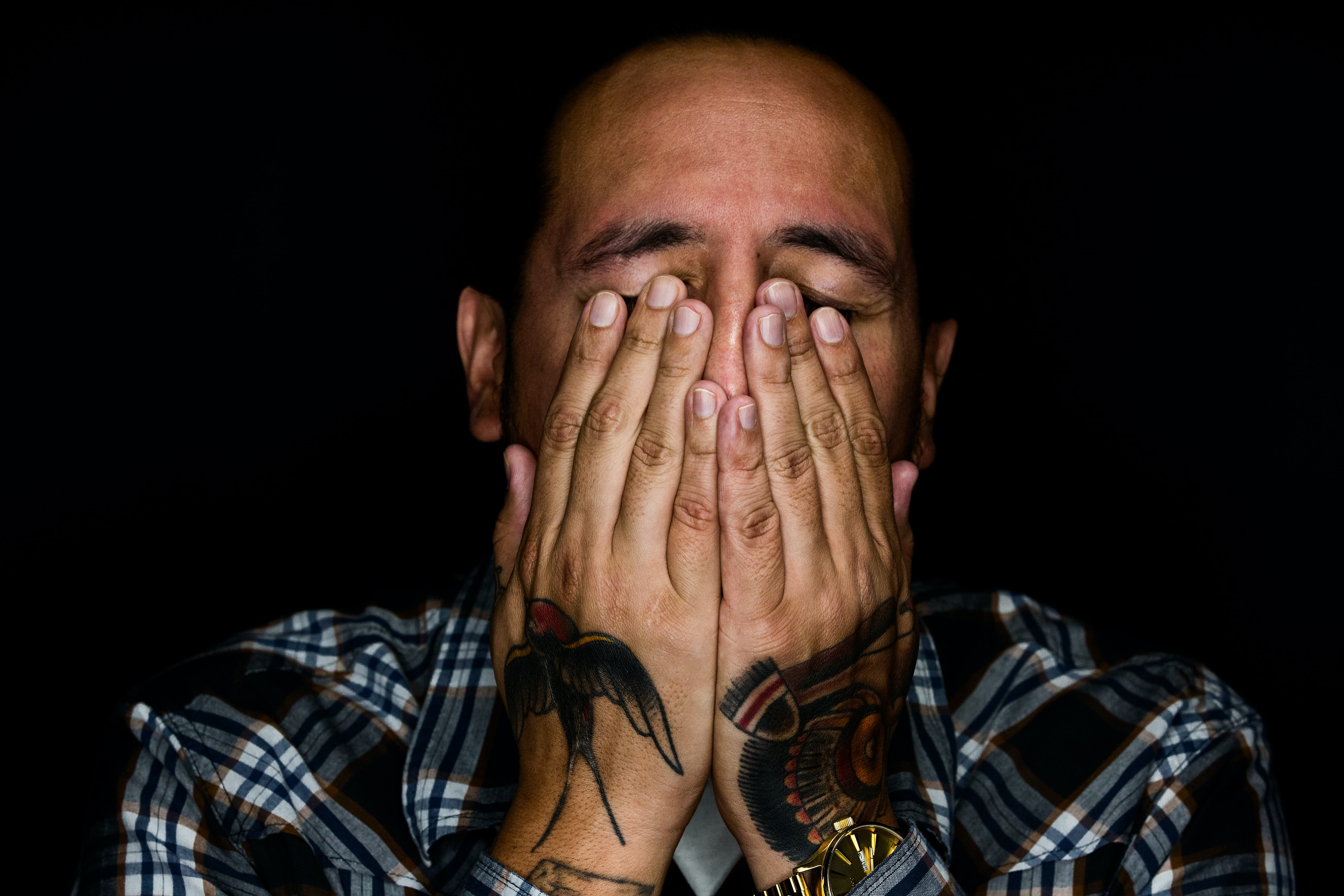 Man in a checkered shirt covering his face with tattooed hands