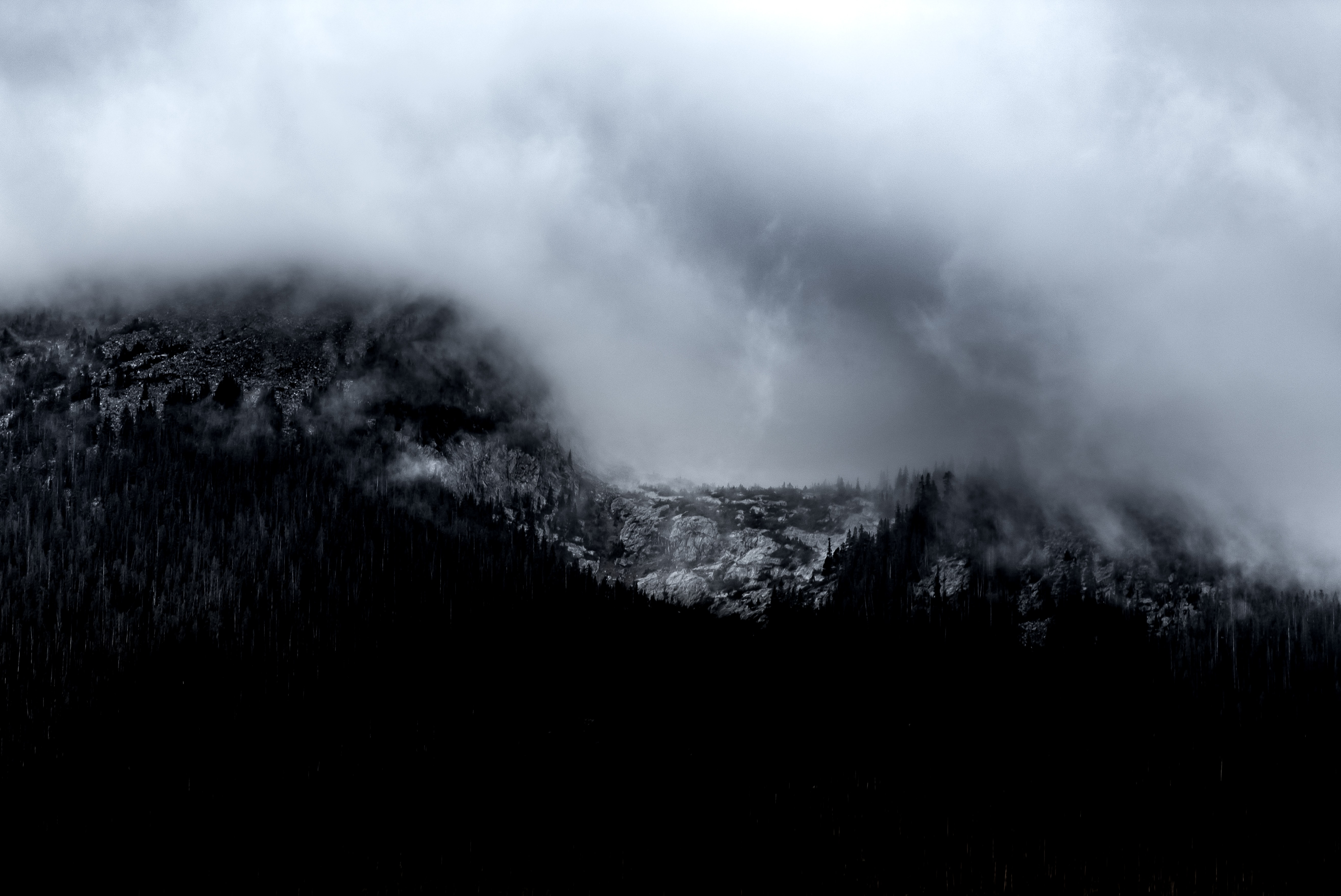 A desaturated shot of heavy clouds gathering over a mountain in Silverthorne