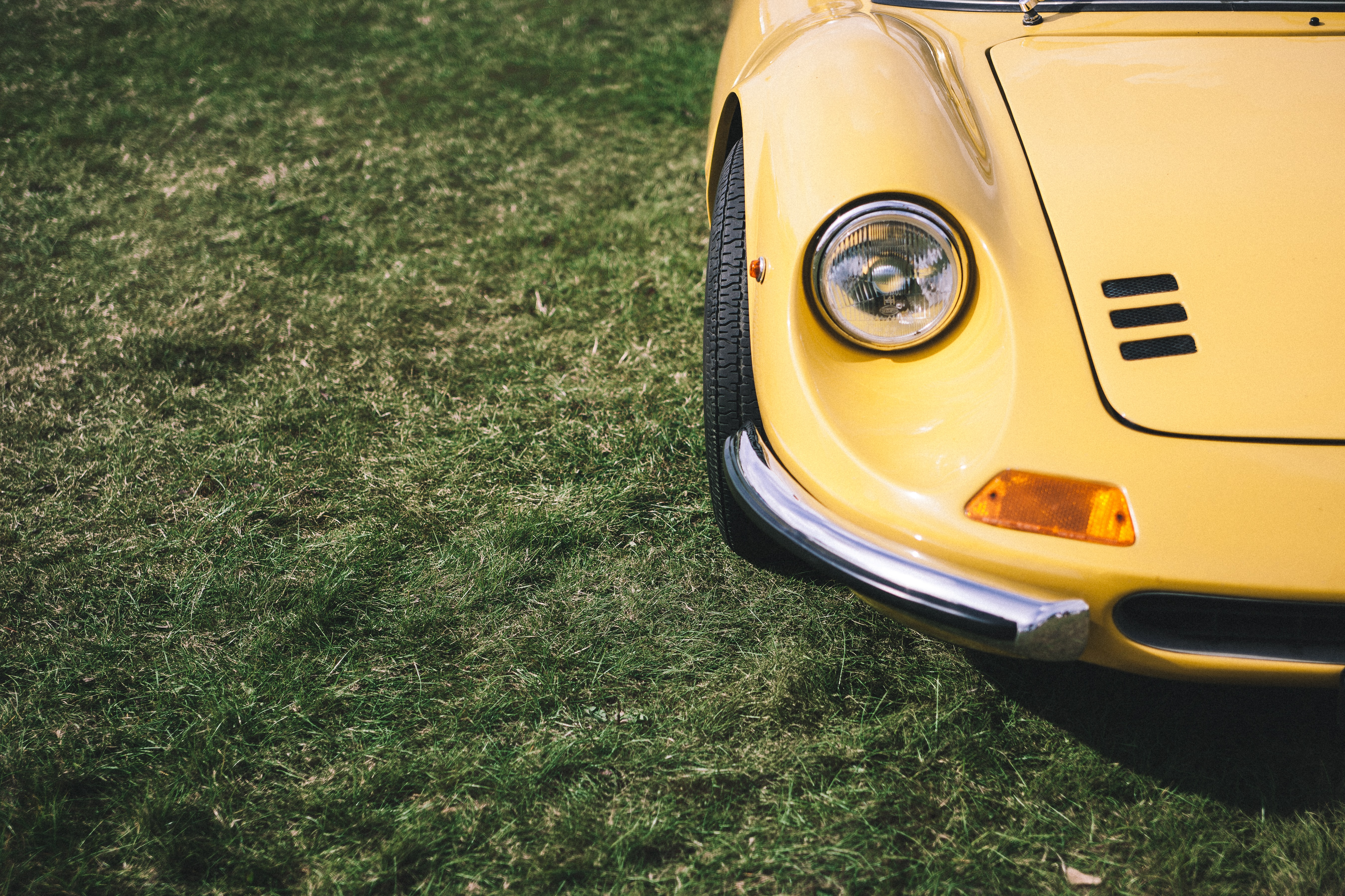 A shot of the front of a classic yellow car parked next to the grass.
