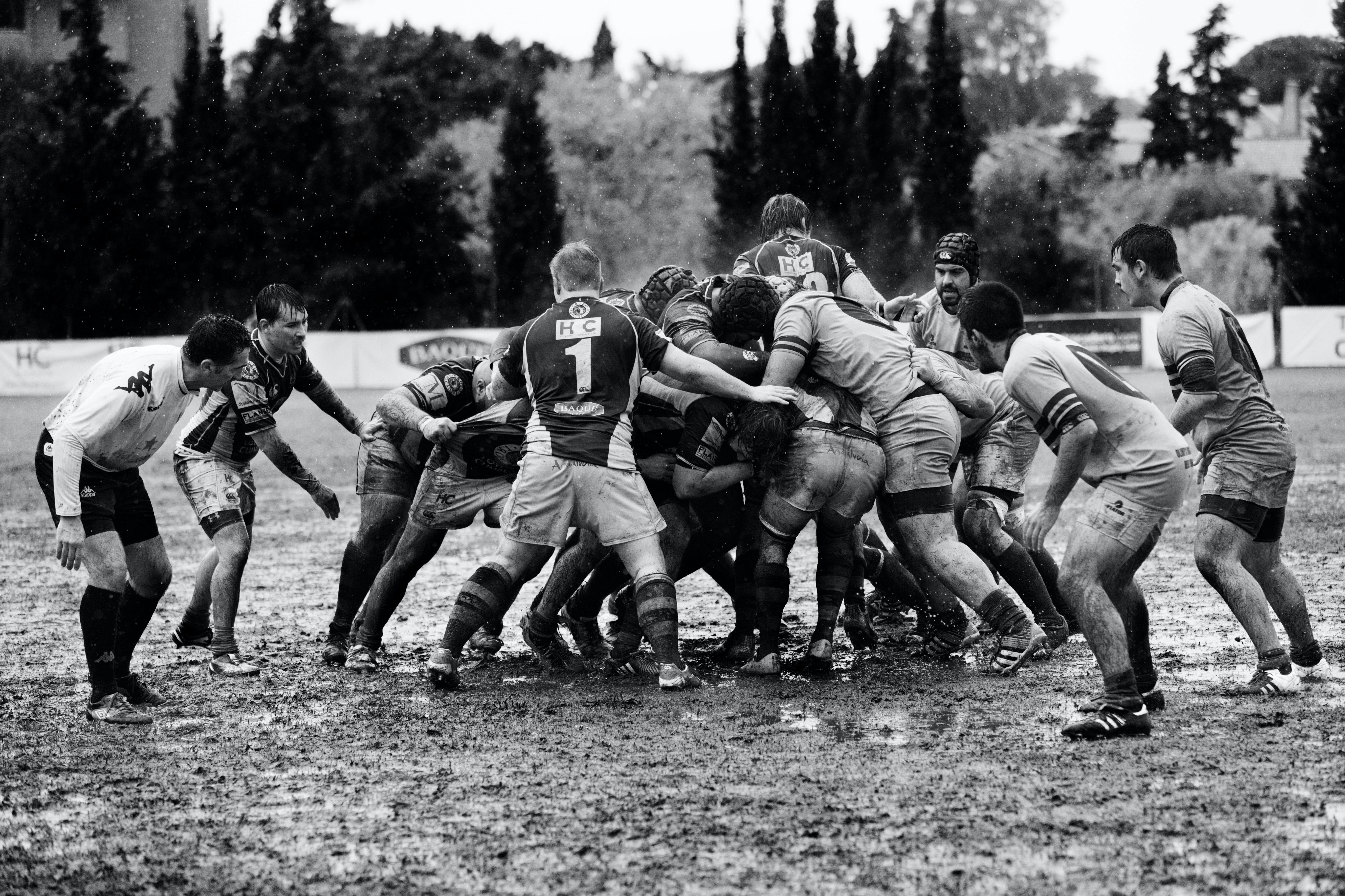 grayscale photography of men playing rugby on muddy land