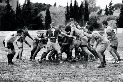 grayscale photography of men playing rugby on muddy land rugby teams background
