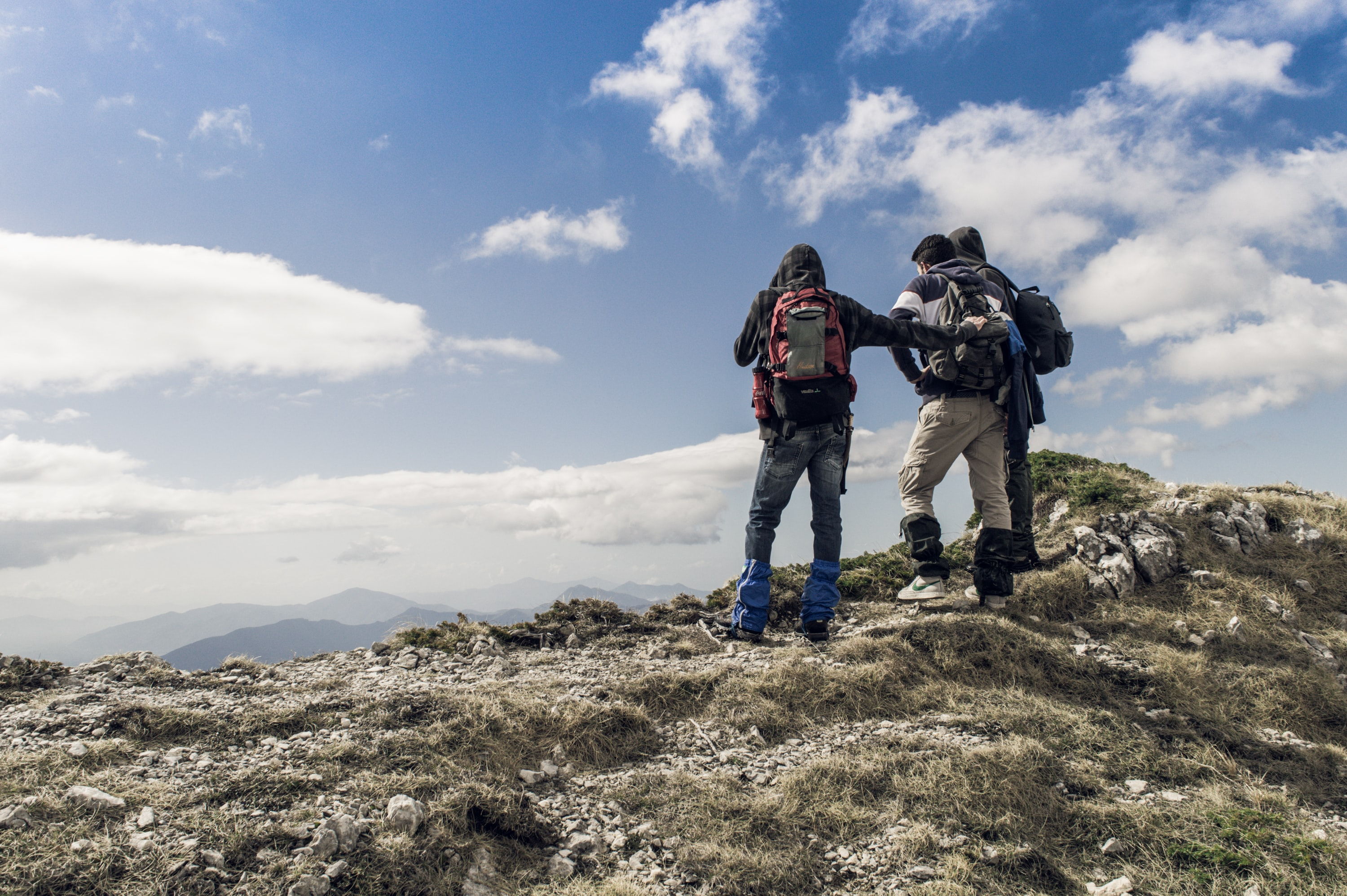 Hikers standing on a rocky mountain peak in Filignano looking at the sky and the hills