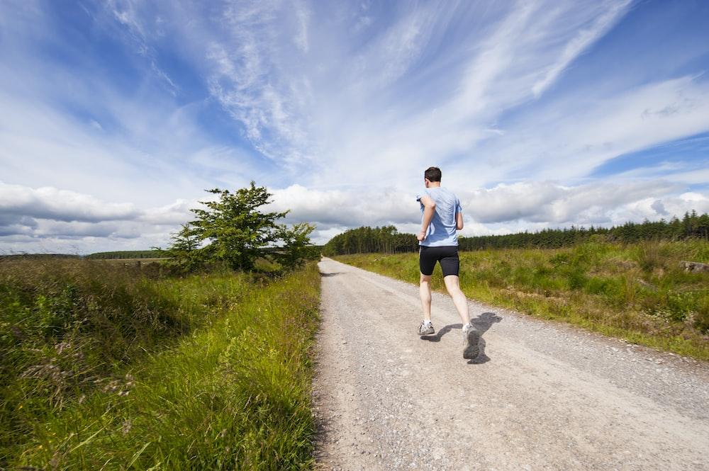man running on road near grass field