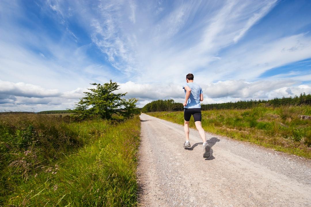 A man running on a dirt path through the grass