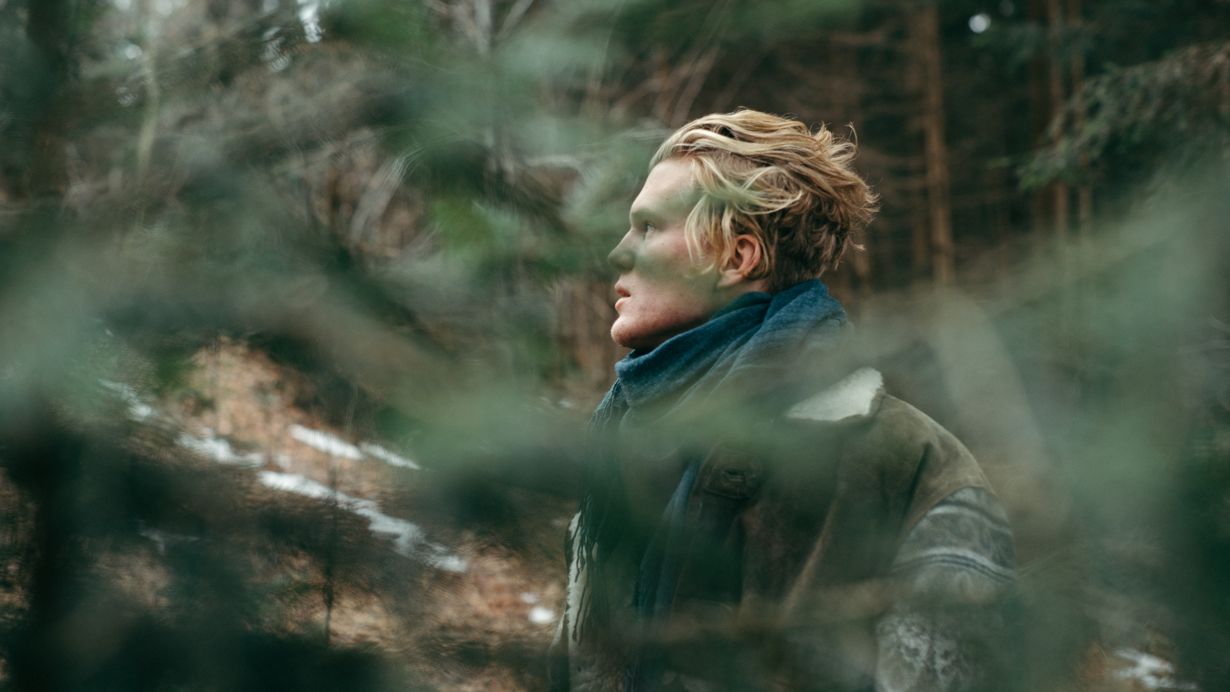 A blonde man wearing a scarf in the forest