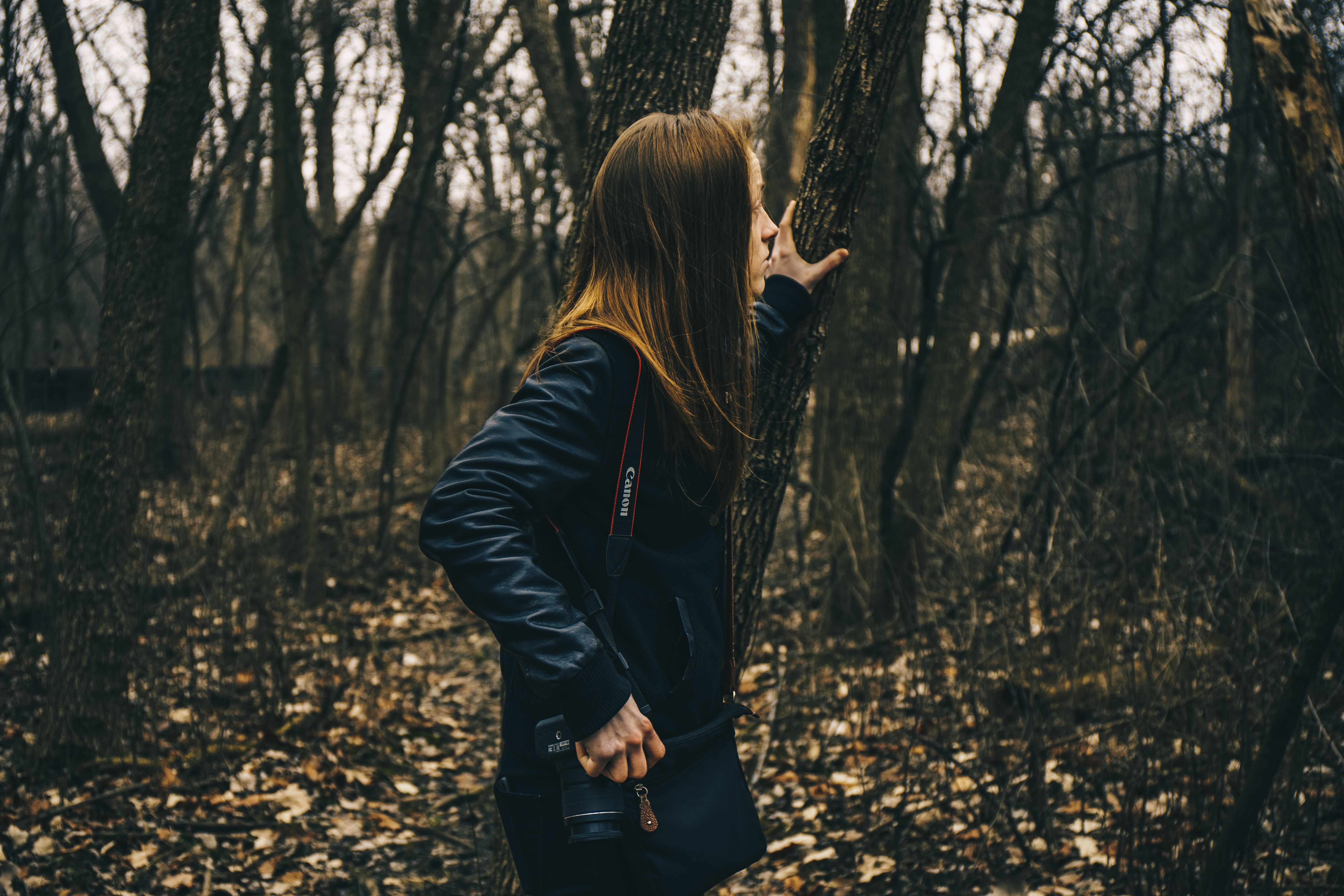 woman in forest holding tree