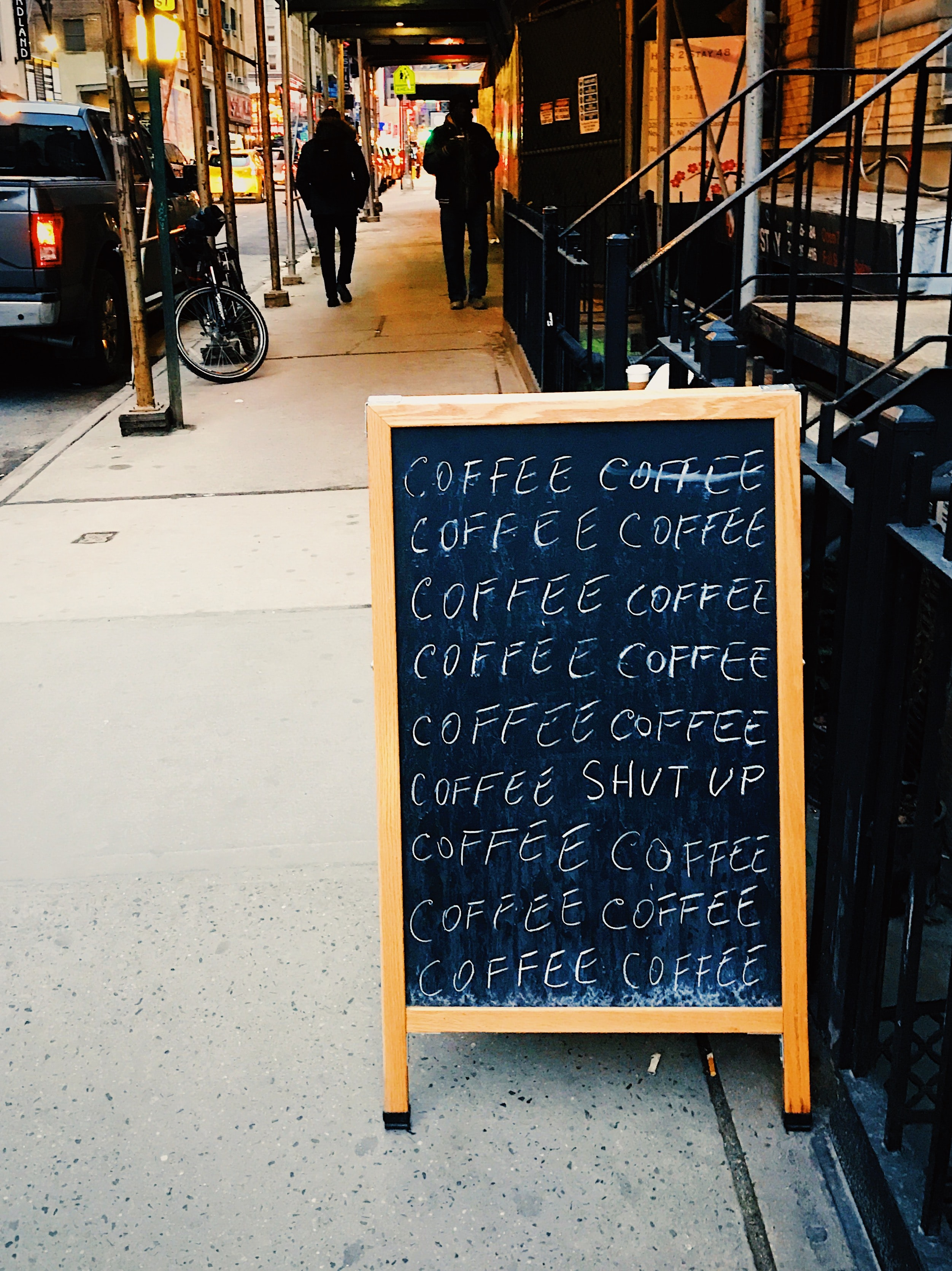 "A chalkboard sign that says ""Coffee,"" written 15 times with ""Shut Up,"" randomly written in the middle."