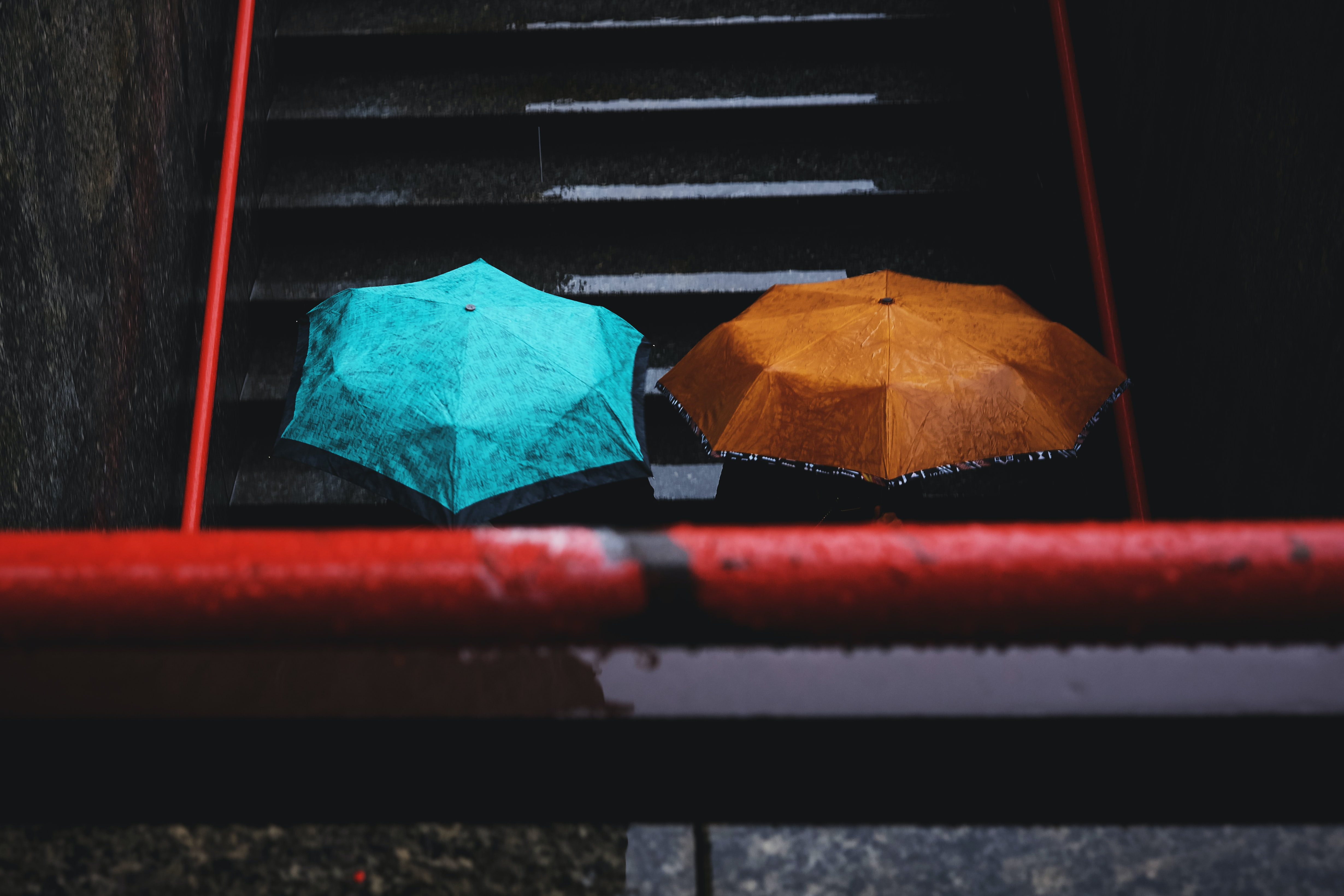 Two people carrying umbrellas on a wet staircase