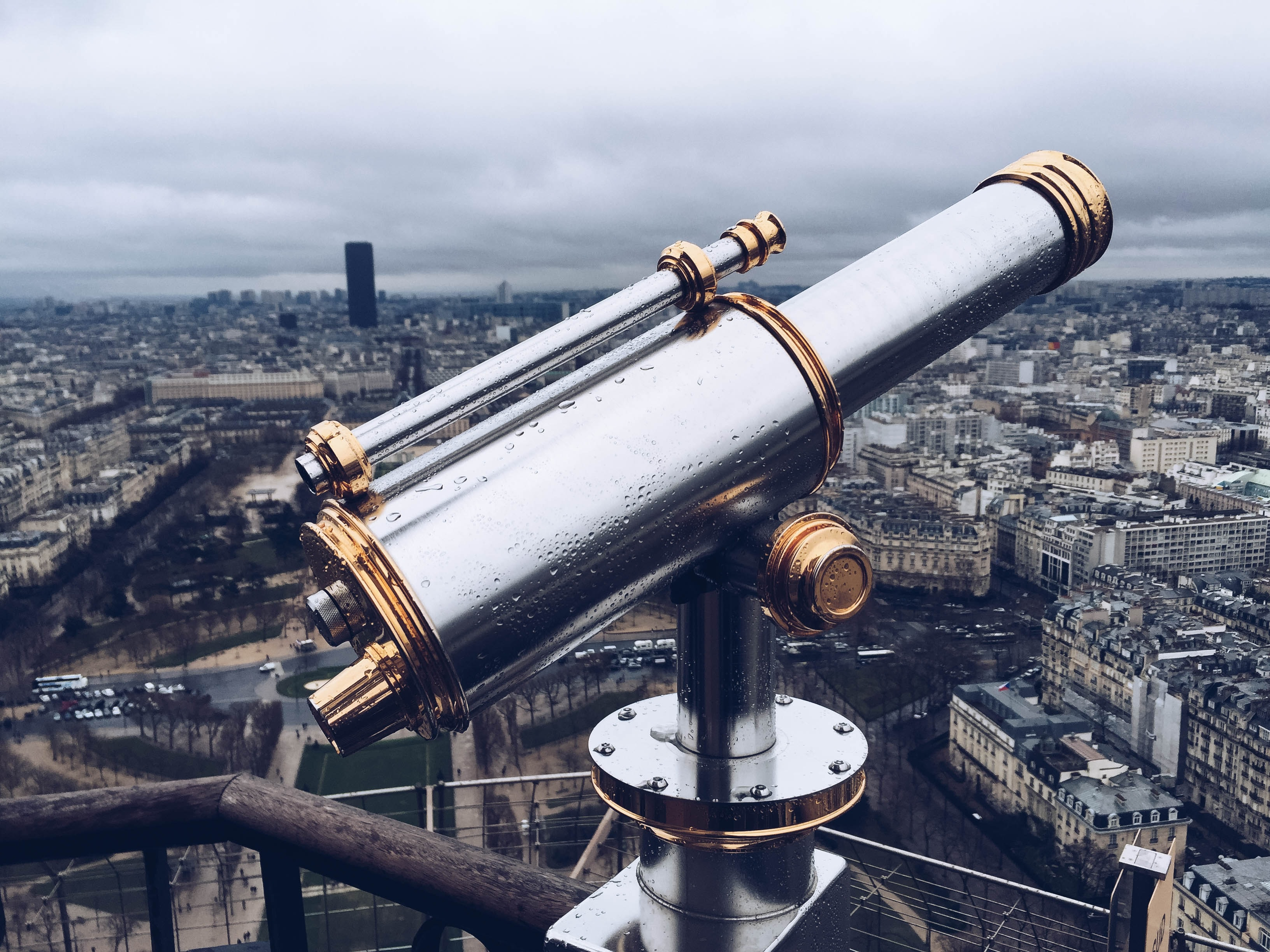 Telescope viewfinder on top of the Eiffel Tower in the rain.