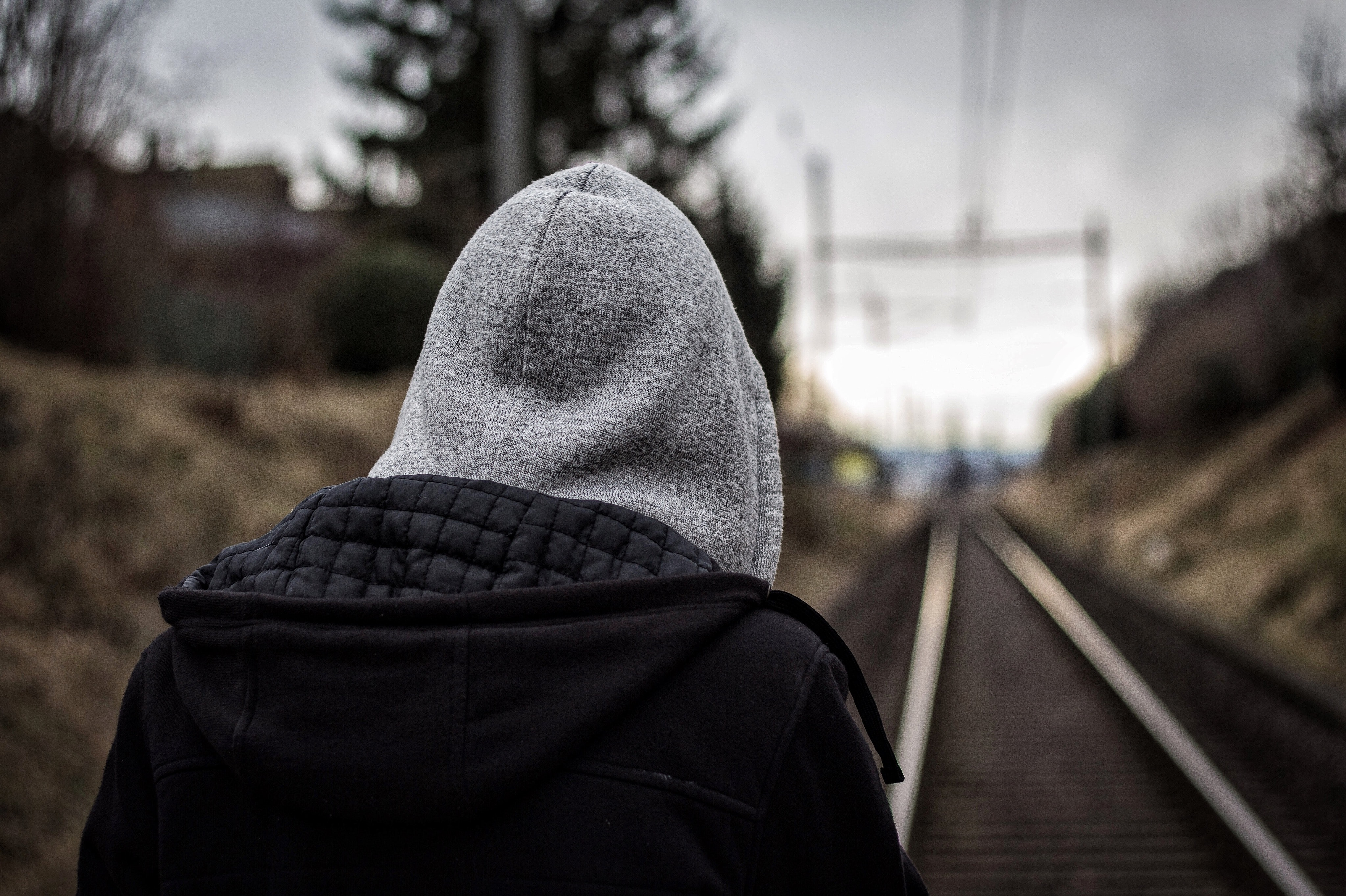 closeup photo of man wearing hoodie in front of train rail