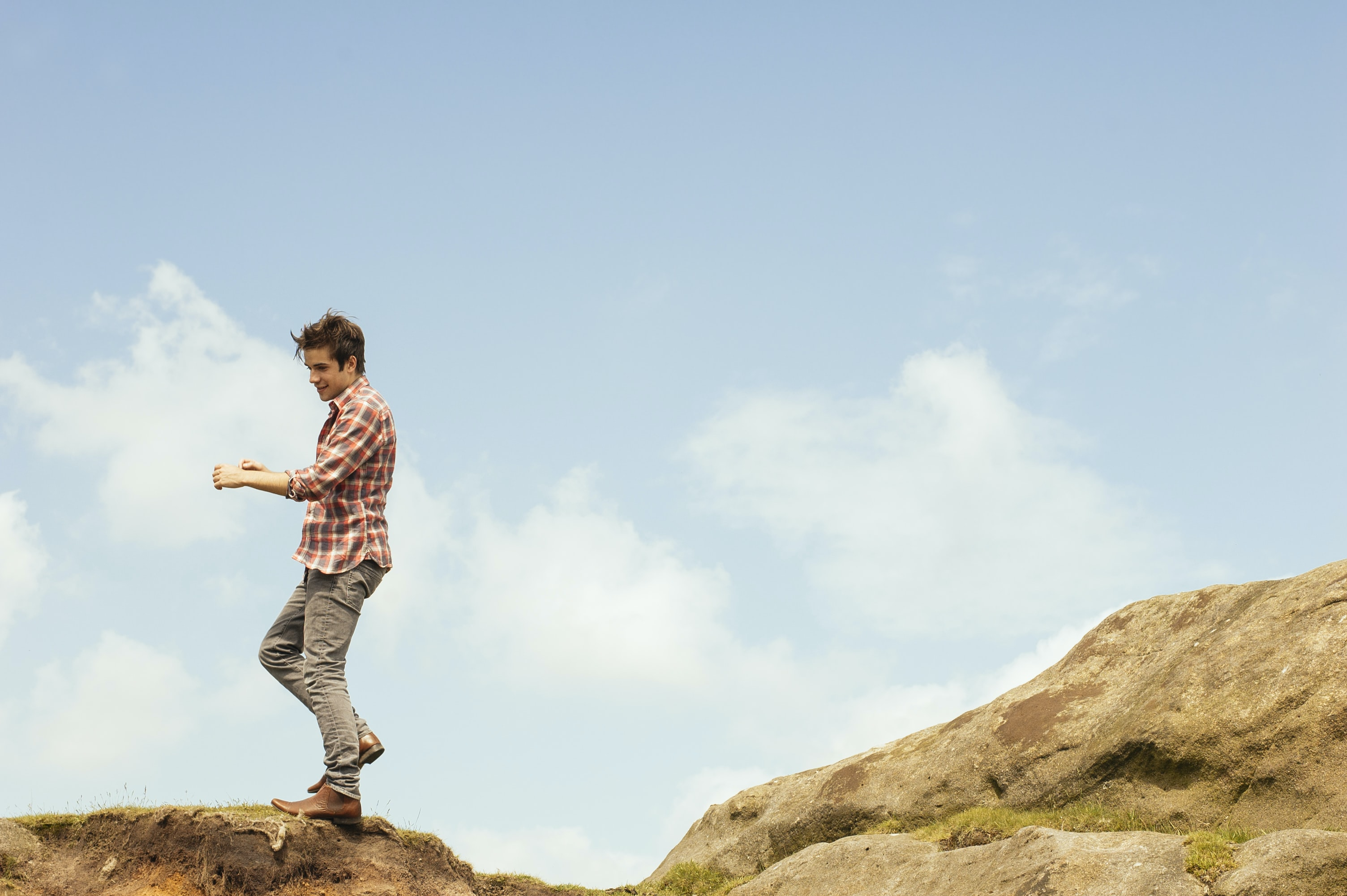 man in red plaid top standing on hilltop during daytime