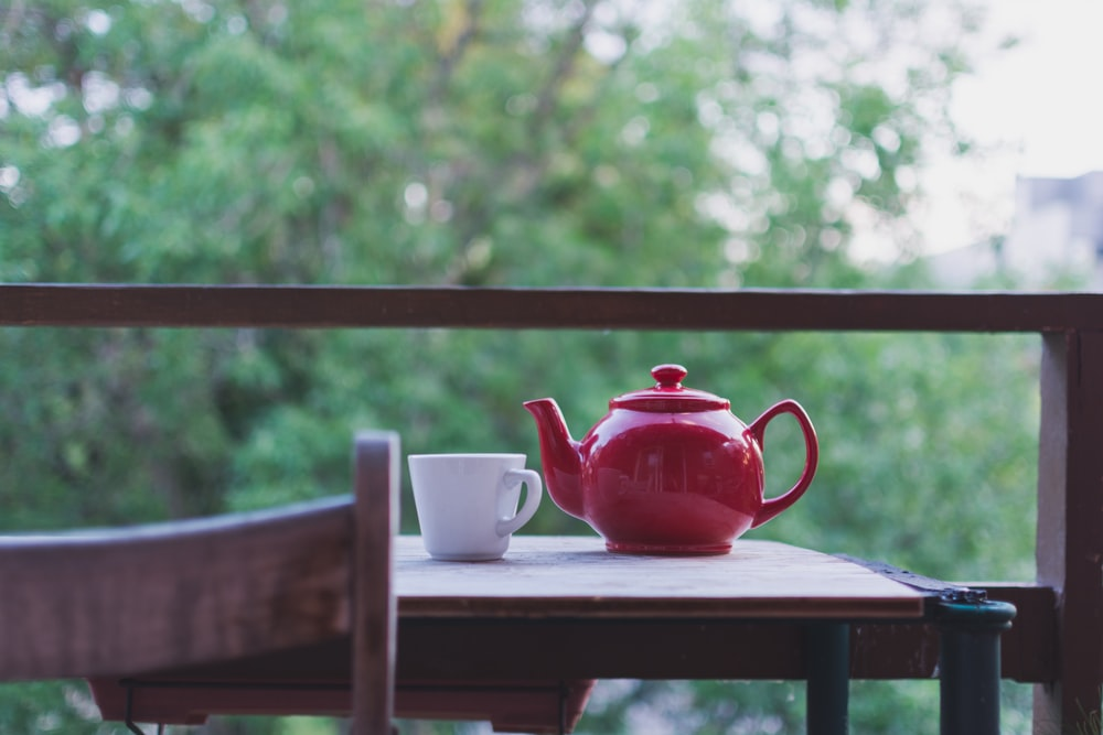 selective focus photo of red ceramic teapot and white ceramic teacup on brown wooden table near tree during daytime
