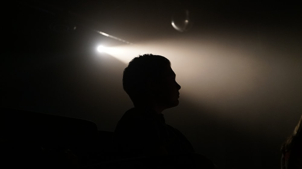 silhouette of person inside dim lighted room