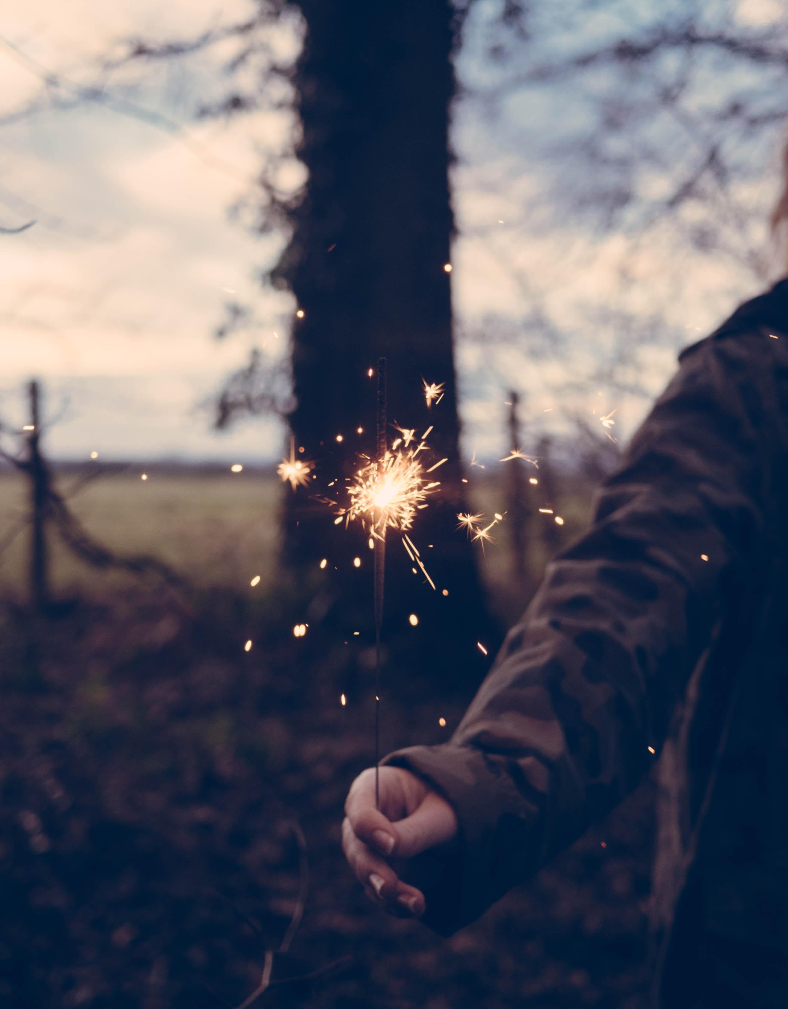 person holding sparkler at daytime
