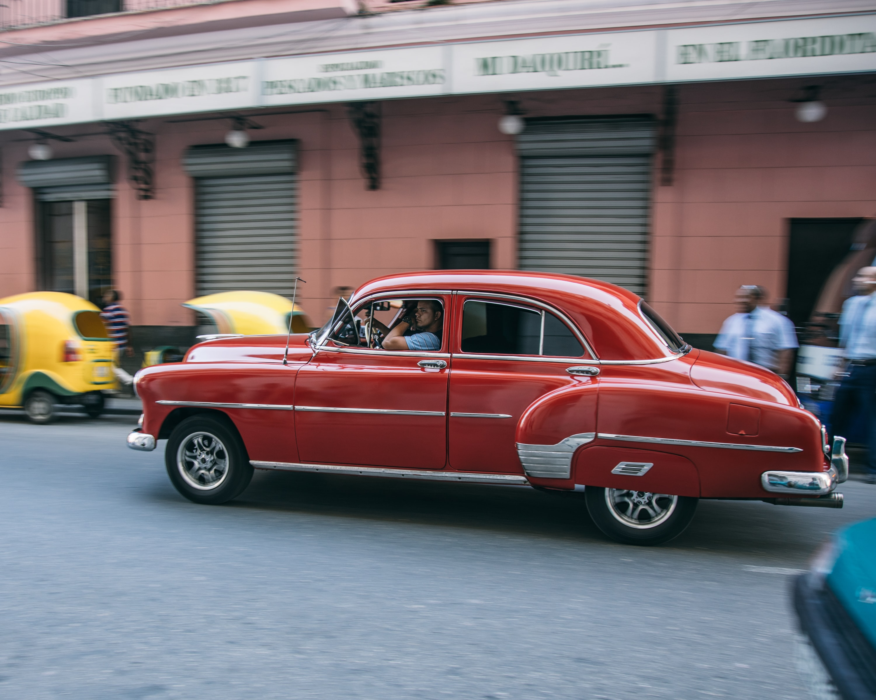 A shiny red vintage car drives through the streets of  La Habana, Cuba