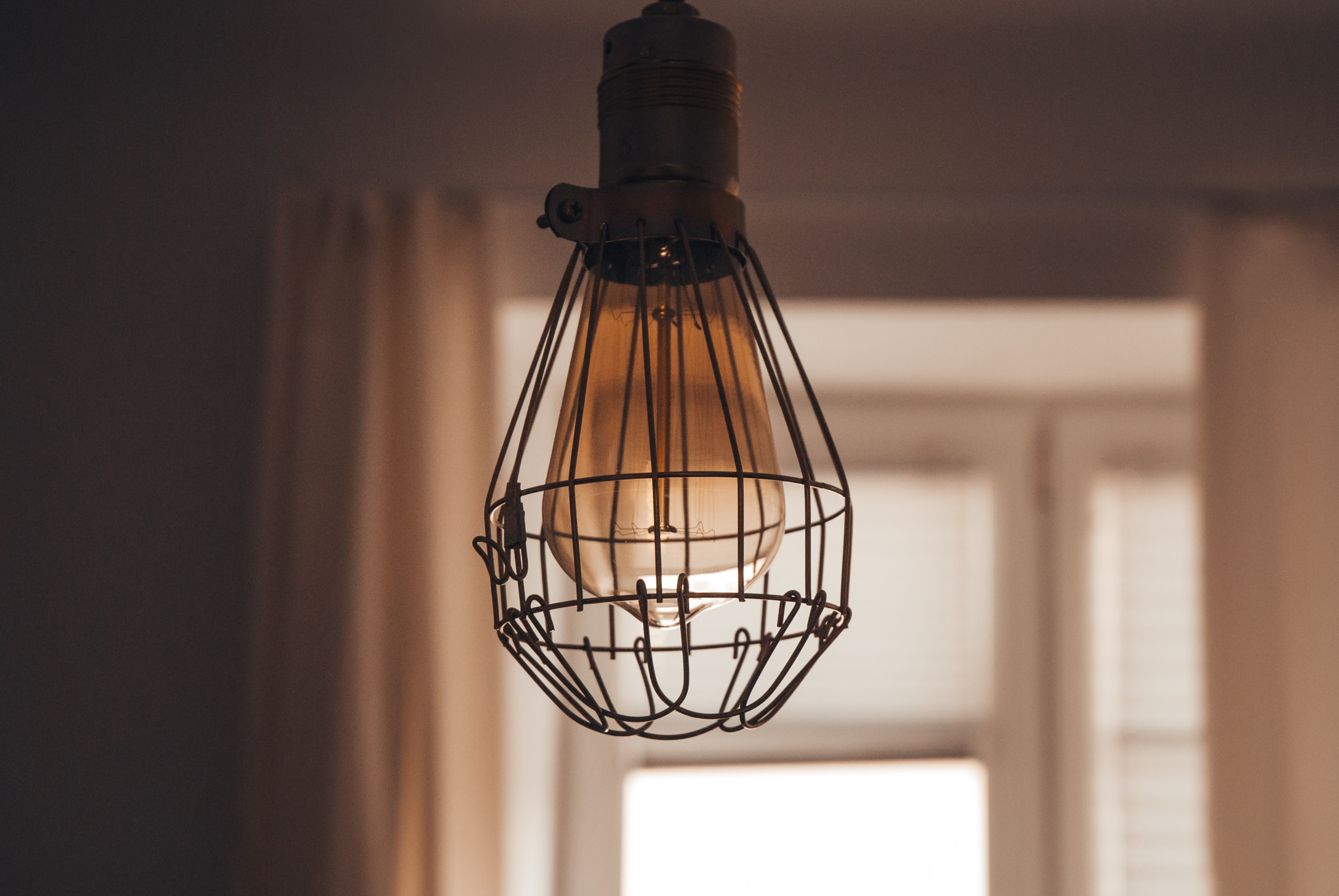 Vintage lightbulb in wire cage casing hanging from a room ceiling