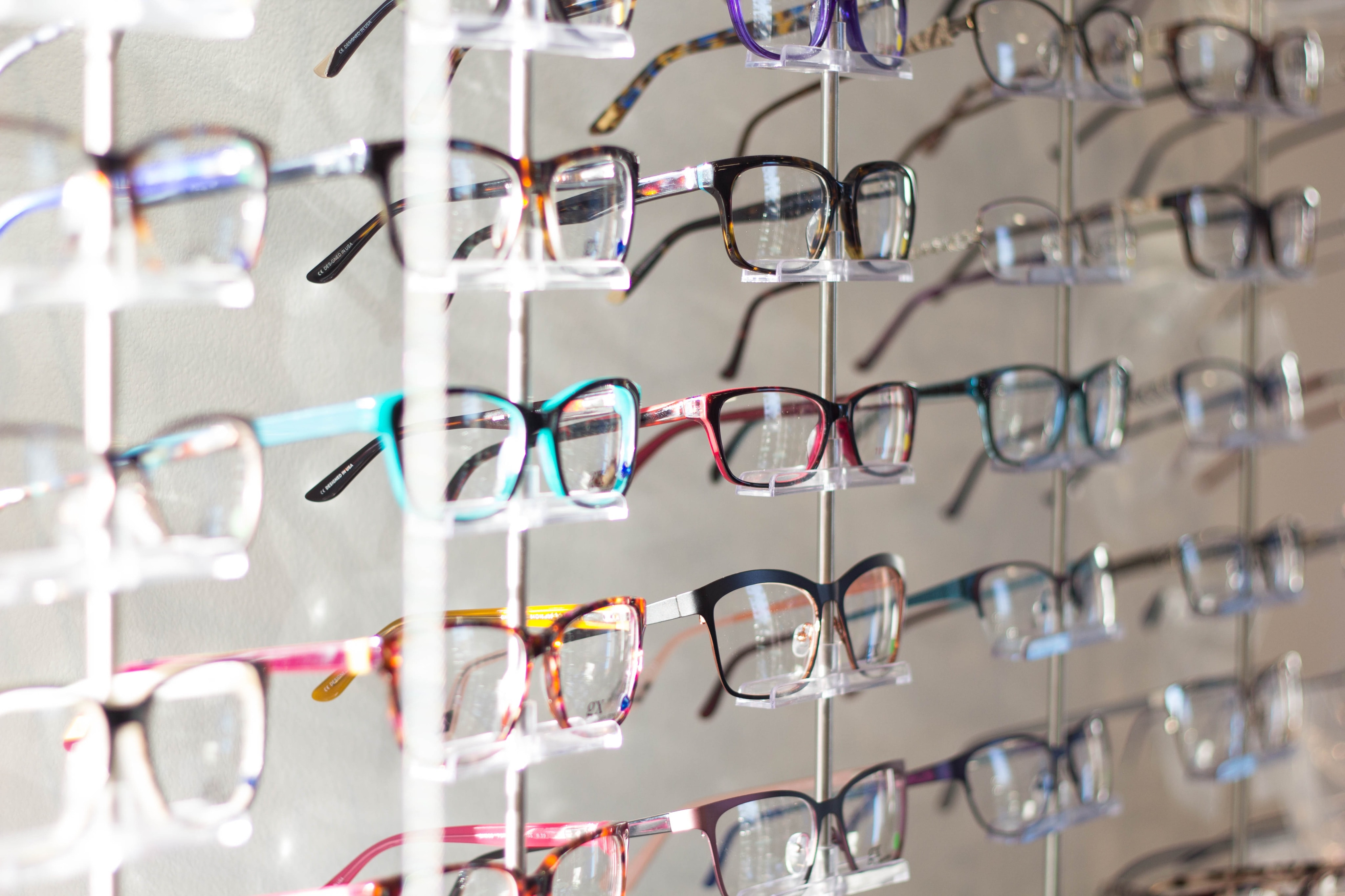 Rows of fashionable eye glasses at an optometrist's office