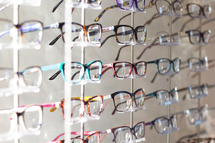 A store shelf stocked with many pairs of eyeglasses.