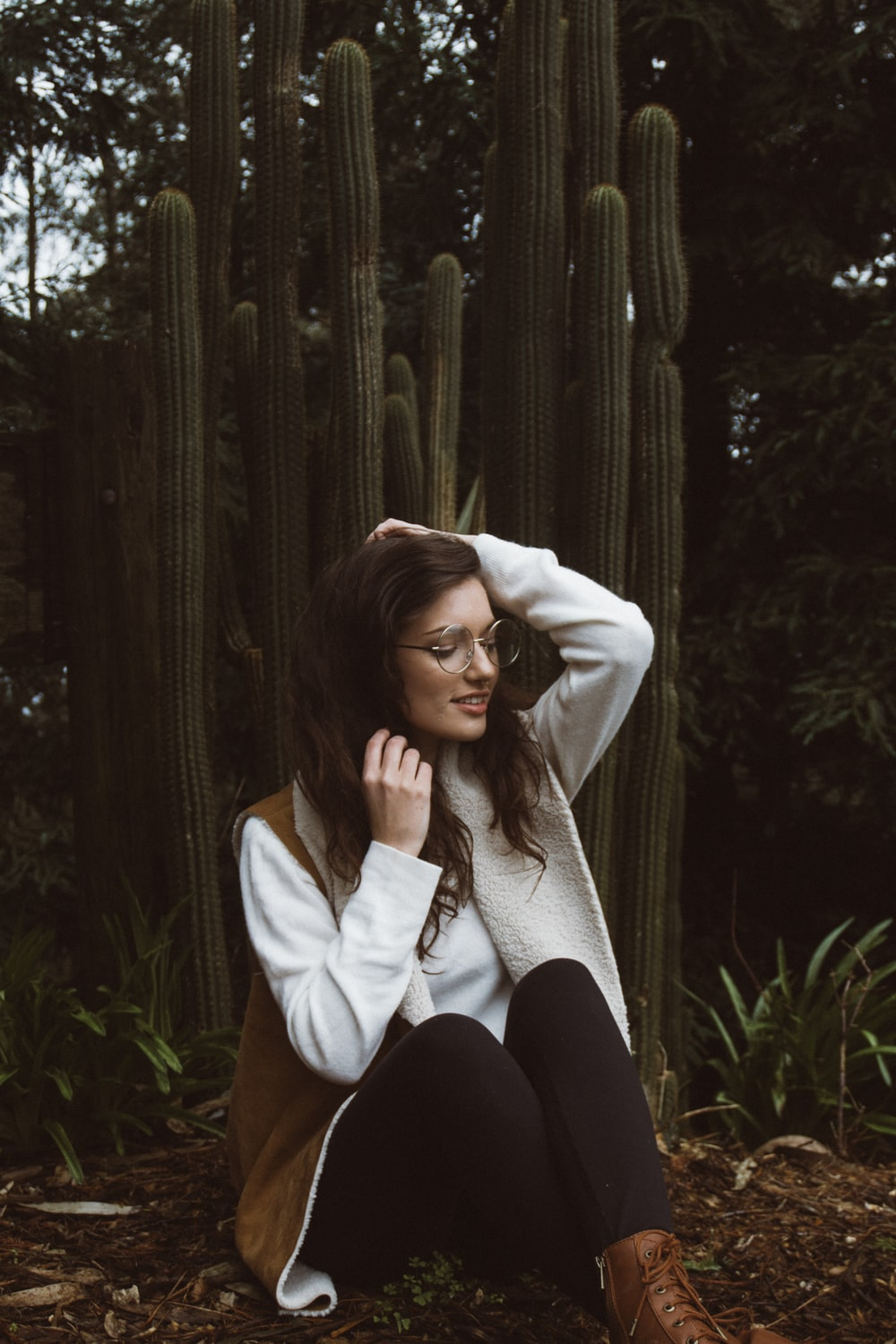 smiling woman wearing brown and white coat sitting beside green cacti plants