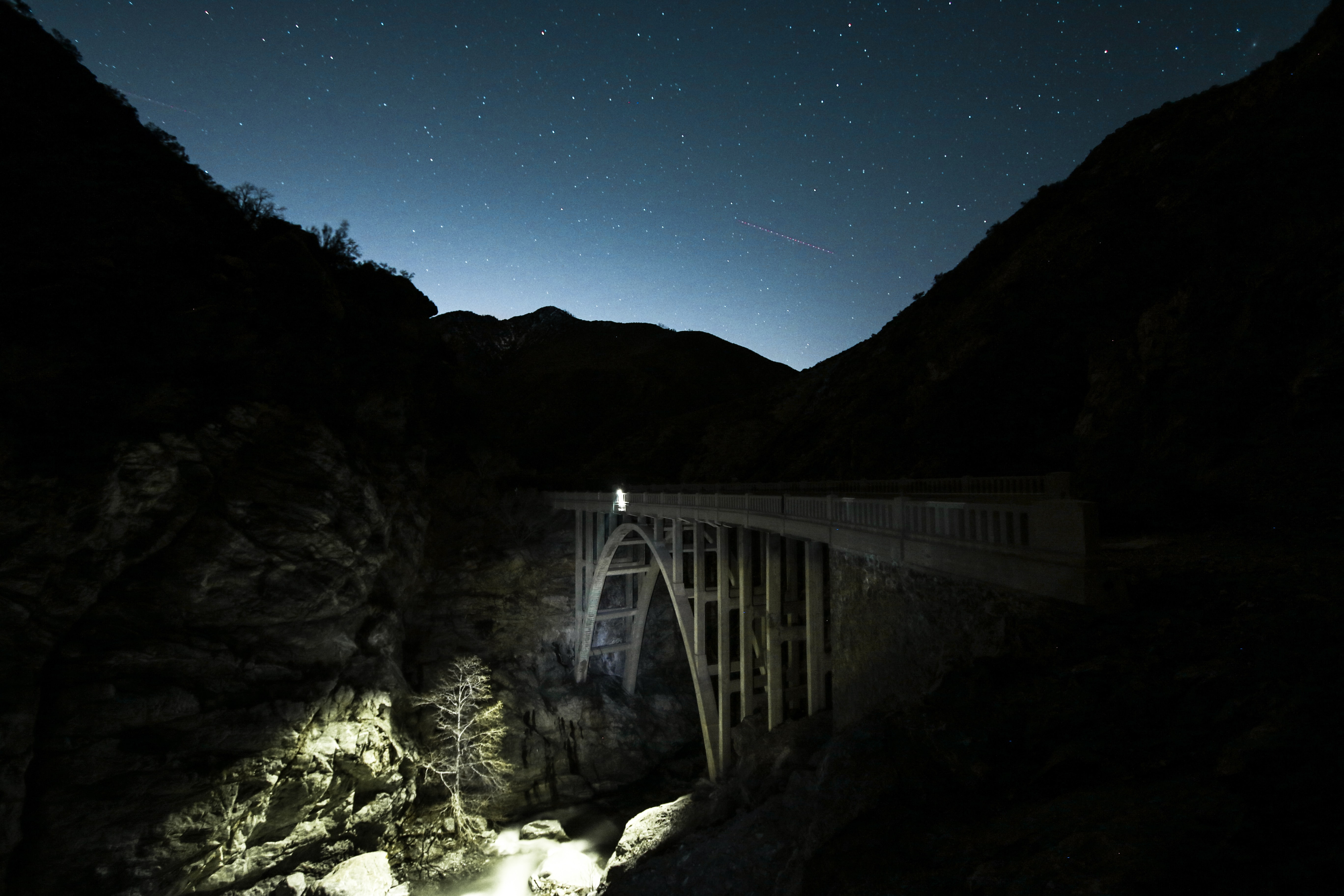 The bridge between mountains with illuminated sky, ground, and stars.