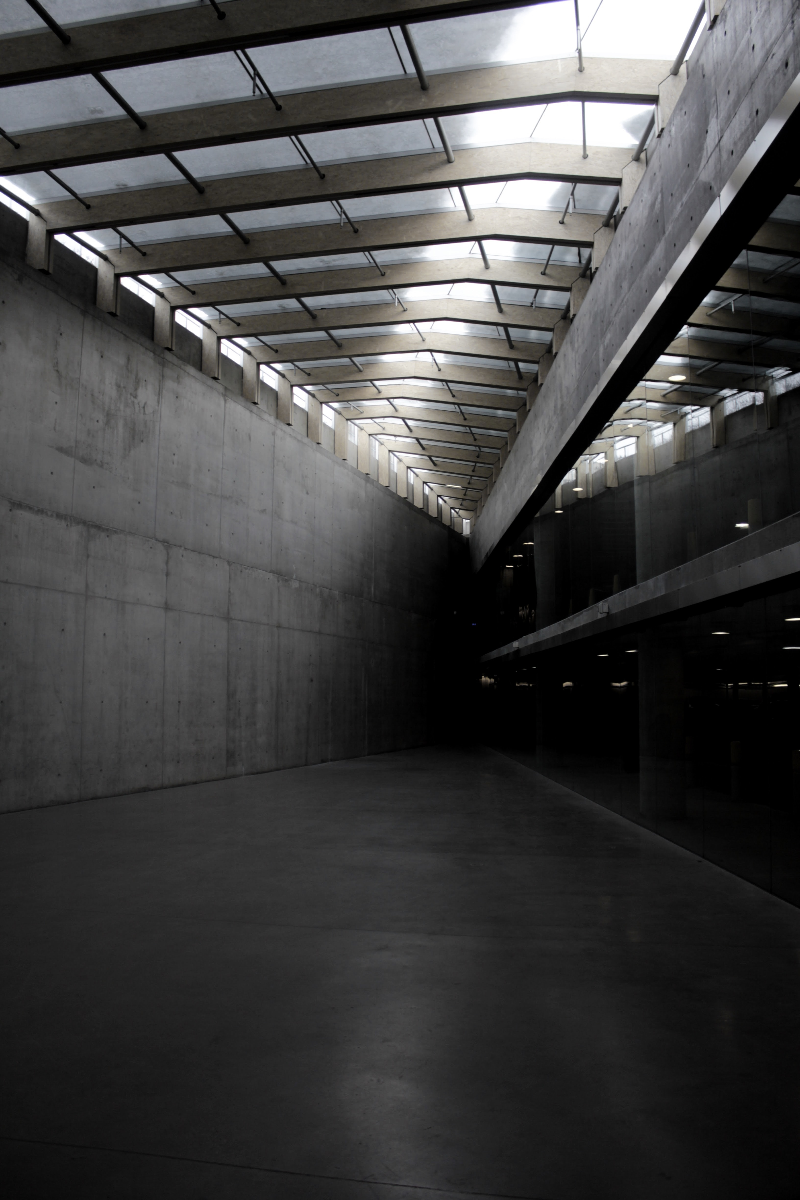 A dark corner in a vast concrete building with a skylight