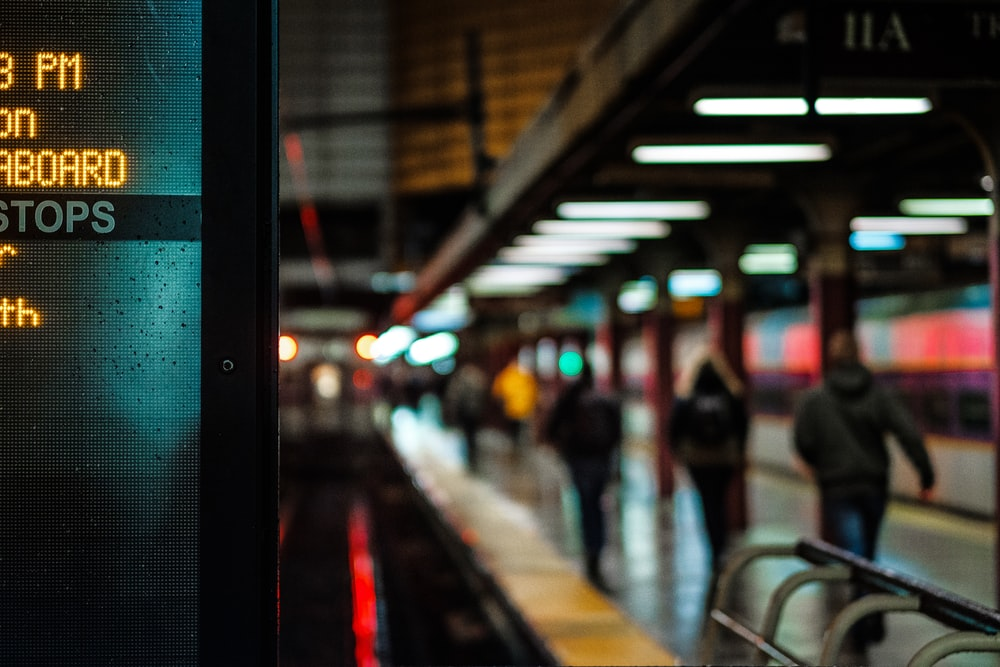 City subway platform lit with signs and commuters walking to their destination