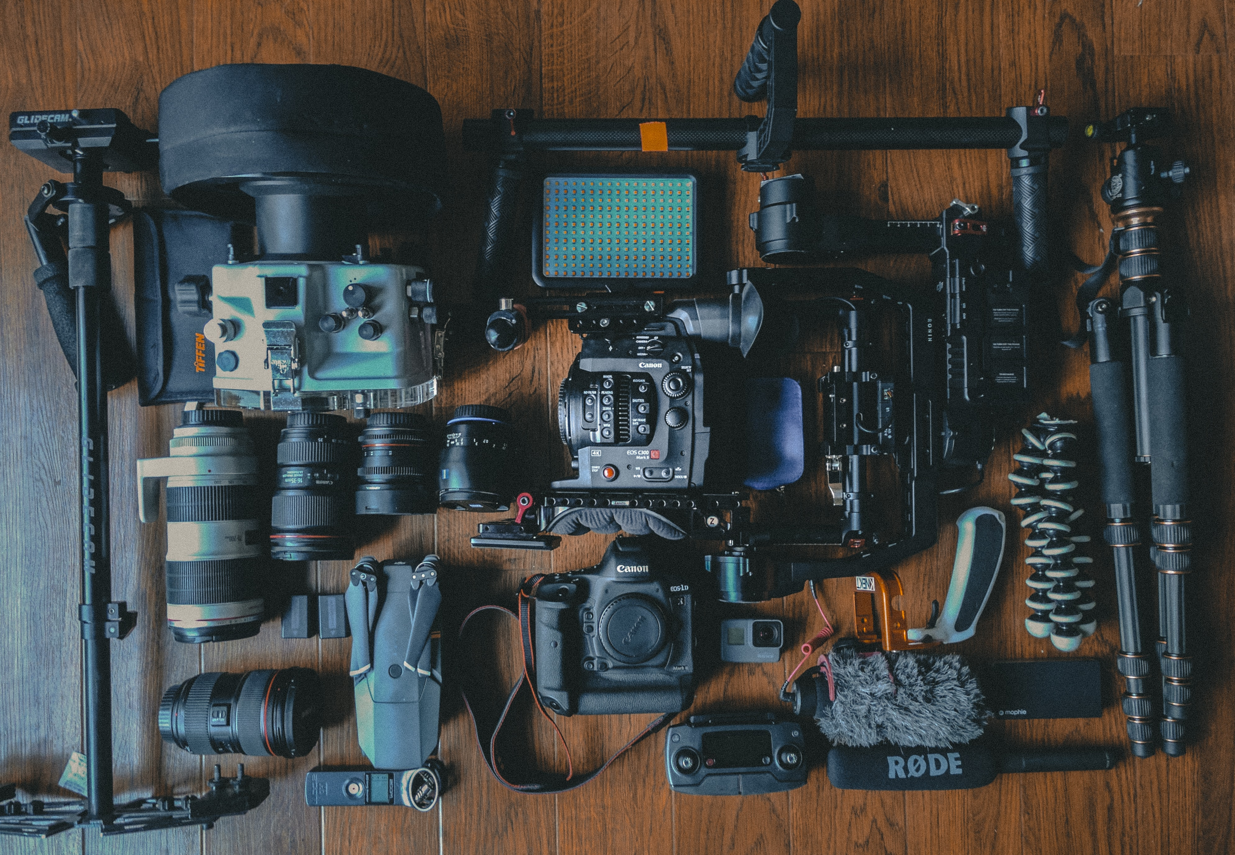 An overhead shot of a variety of photography equipment on a wooden surface
