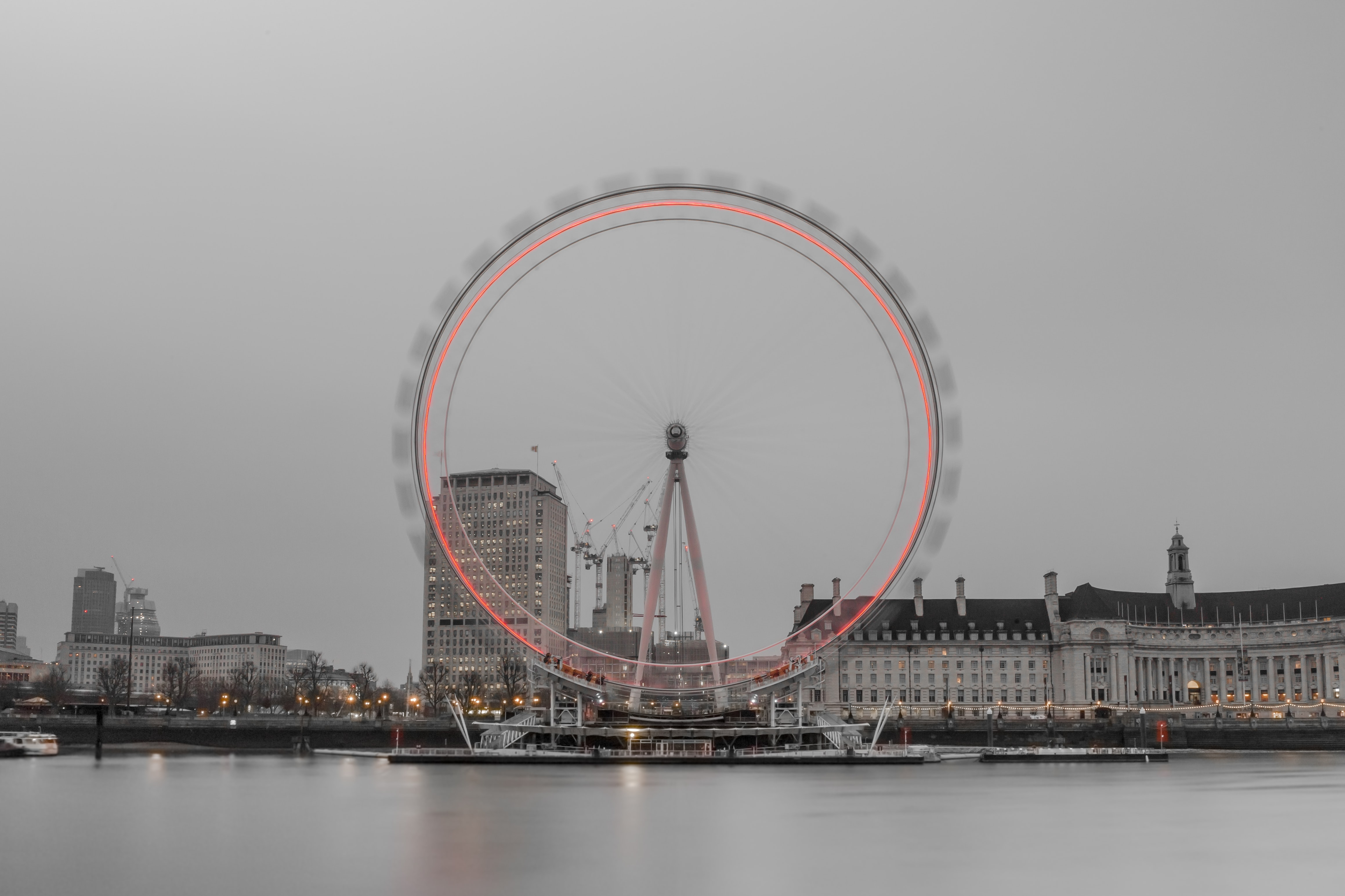 A waterfront background taken at dusk, featuring the London Eye ferris wheel