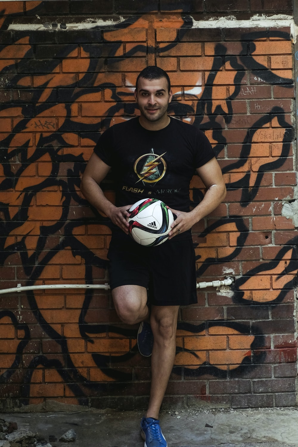 man leaning on wall holding velleyball