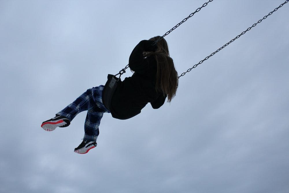 girl swinging during daytime