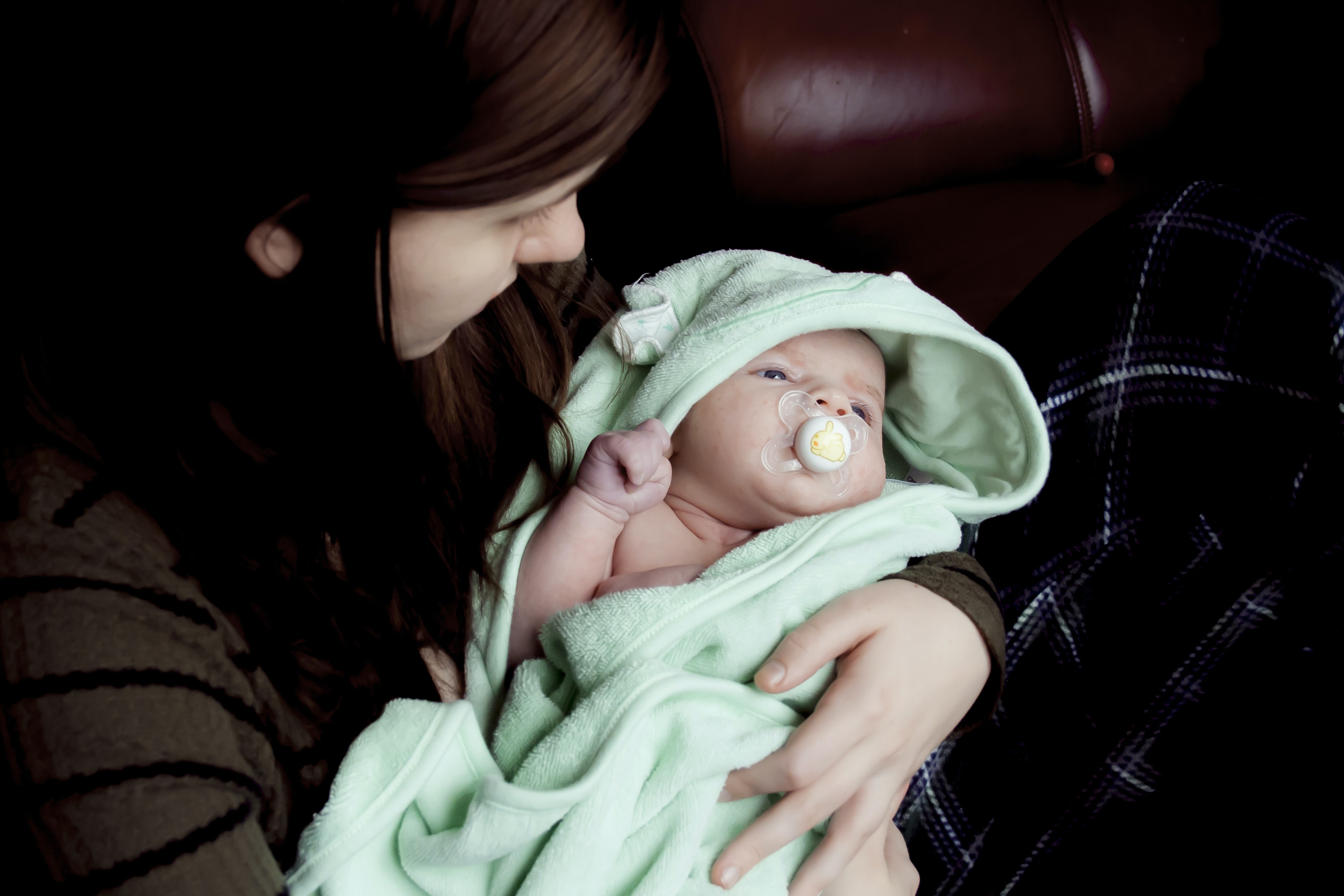 Infant lying in a teal blanket being cradled by a woman with reddish brown hair