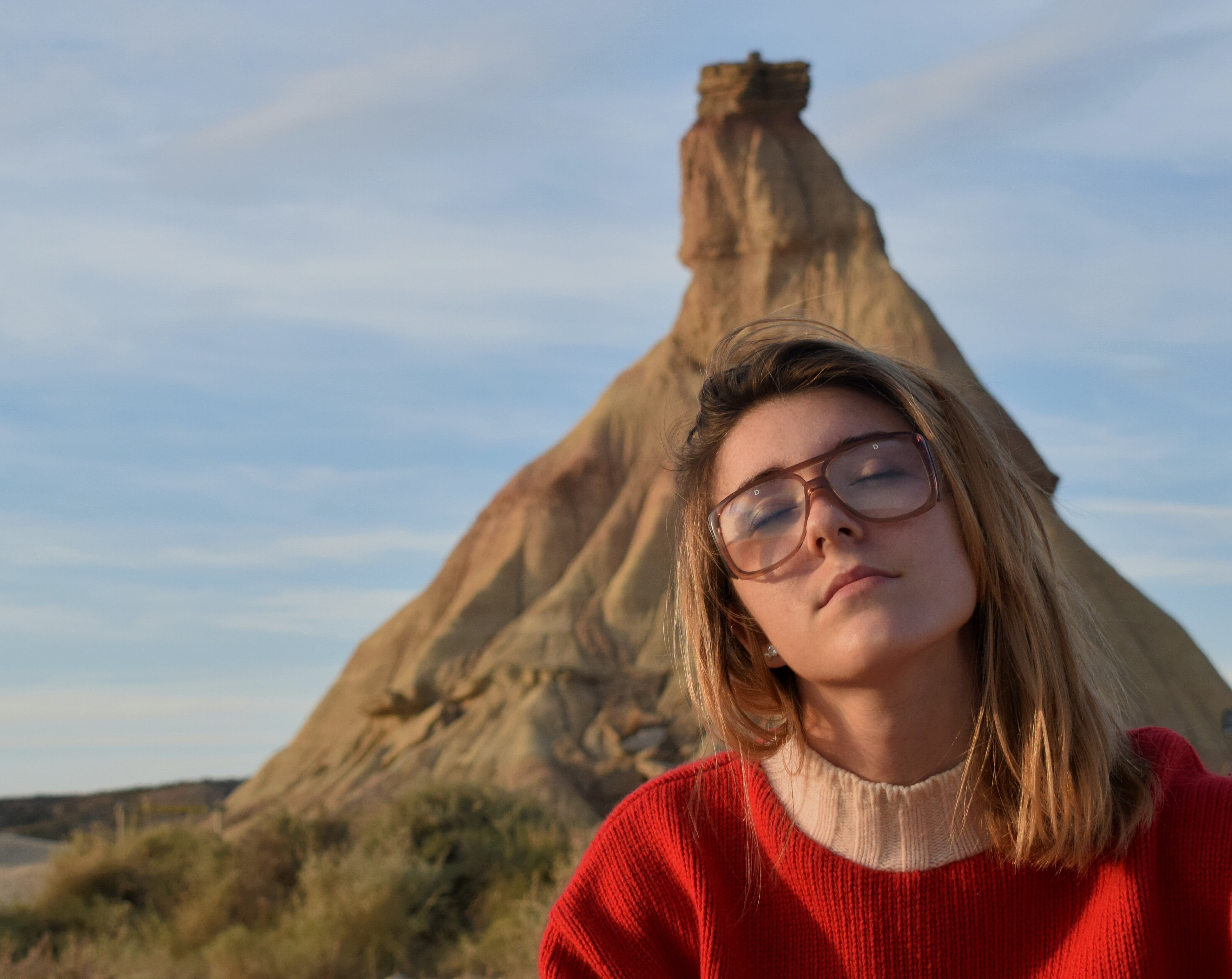 A woman wearing glasses and a red sweater sitting in front of  Bardenas Reales