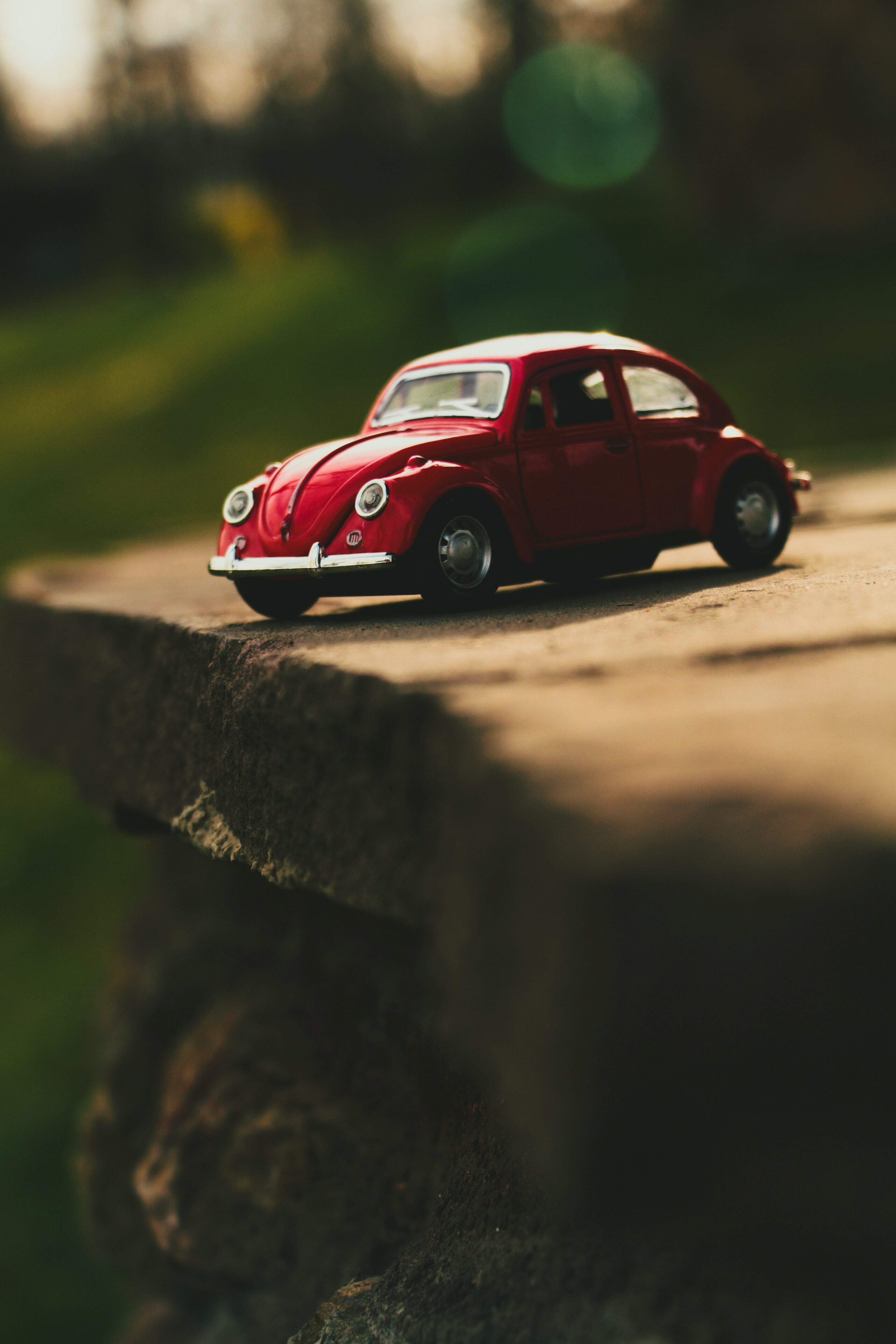 red Volkswagen Beetle scale model on grey concrete board