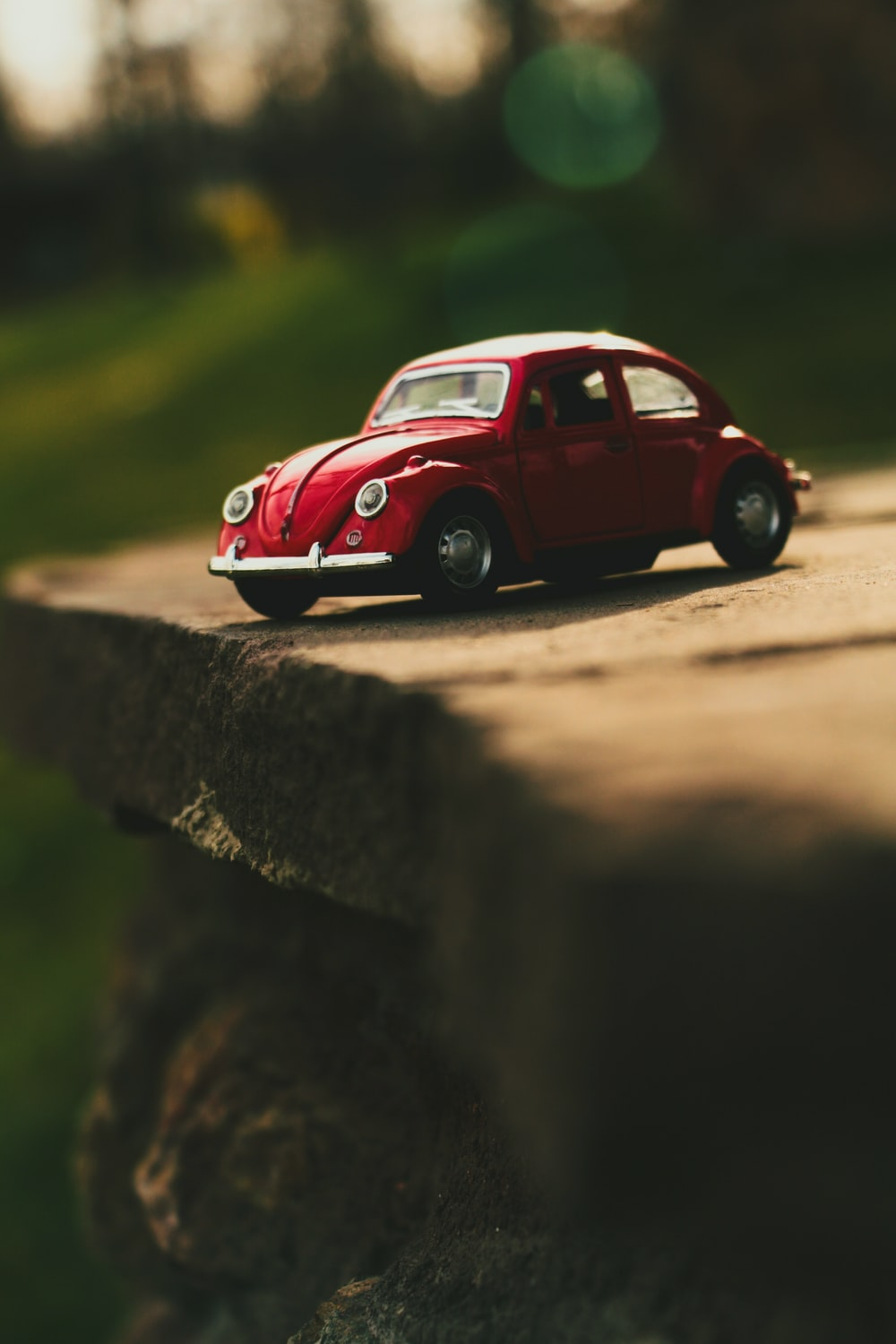 red Volkswagen Beetle scale model on grey concrete board