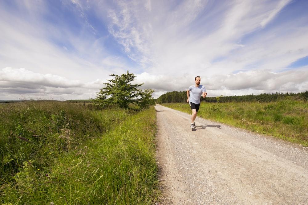 man running on dirt road under cloudy skies